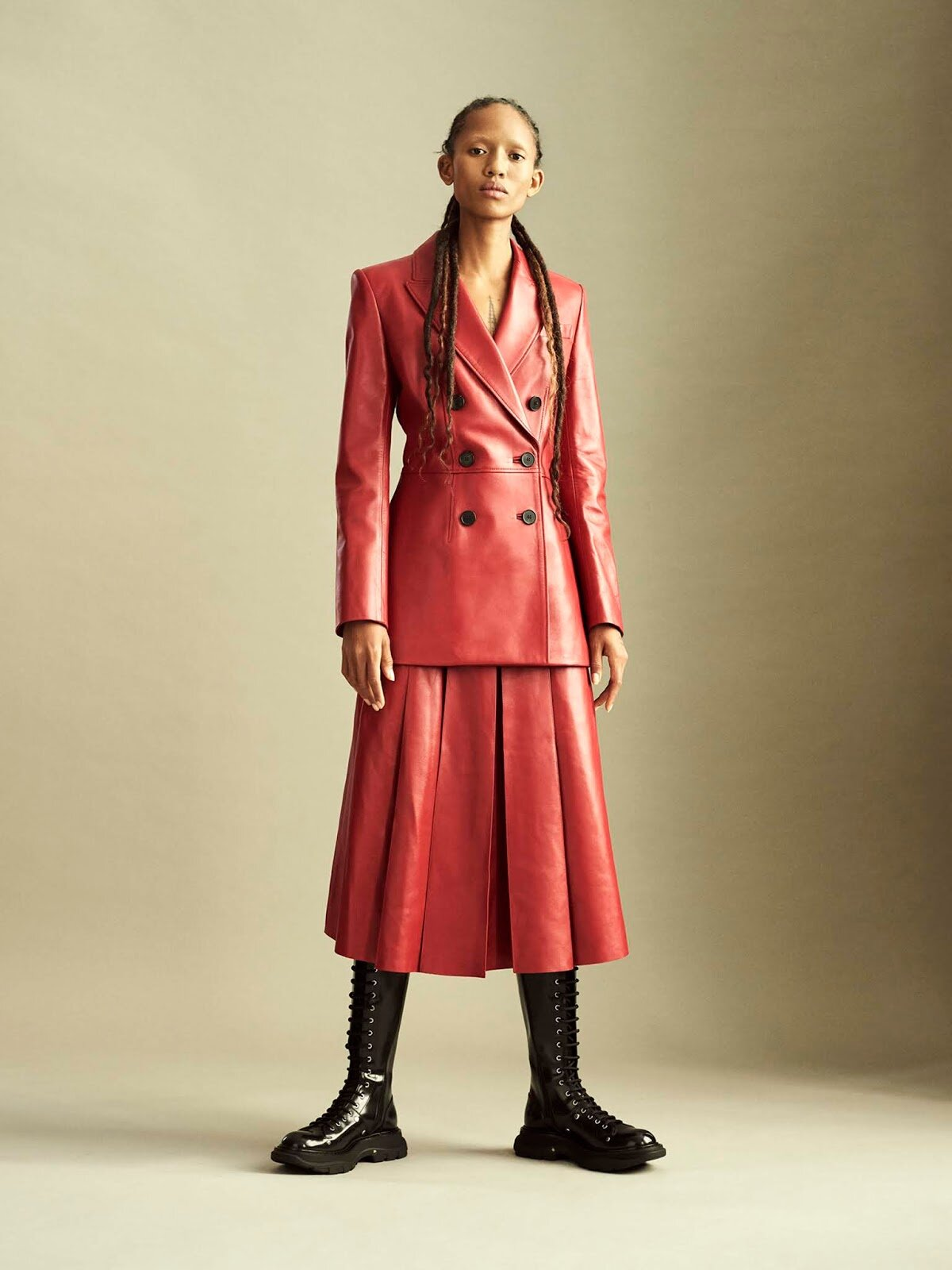 Subverting the timeless jacket-and-pleated-skirt combination by rendering it in bold scarlet leather, Alexander McQueen's Sarah Burton lends a punkish spirit to classic workwear.  Jacket, skirt, and boots, all Alexander McQueen.  Adesuwa Aighewi by Philip Messmann.
