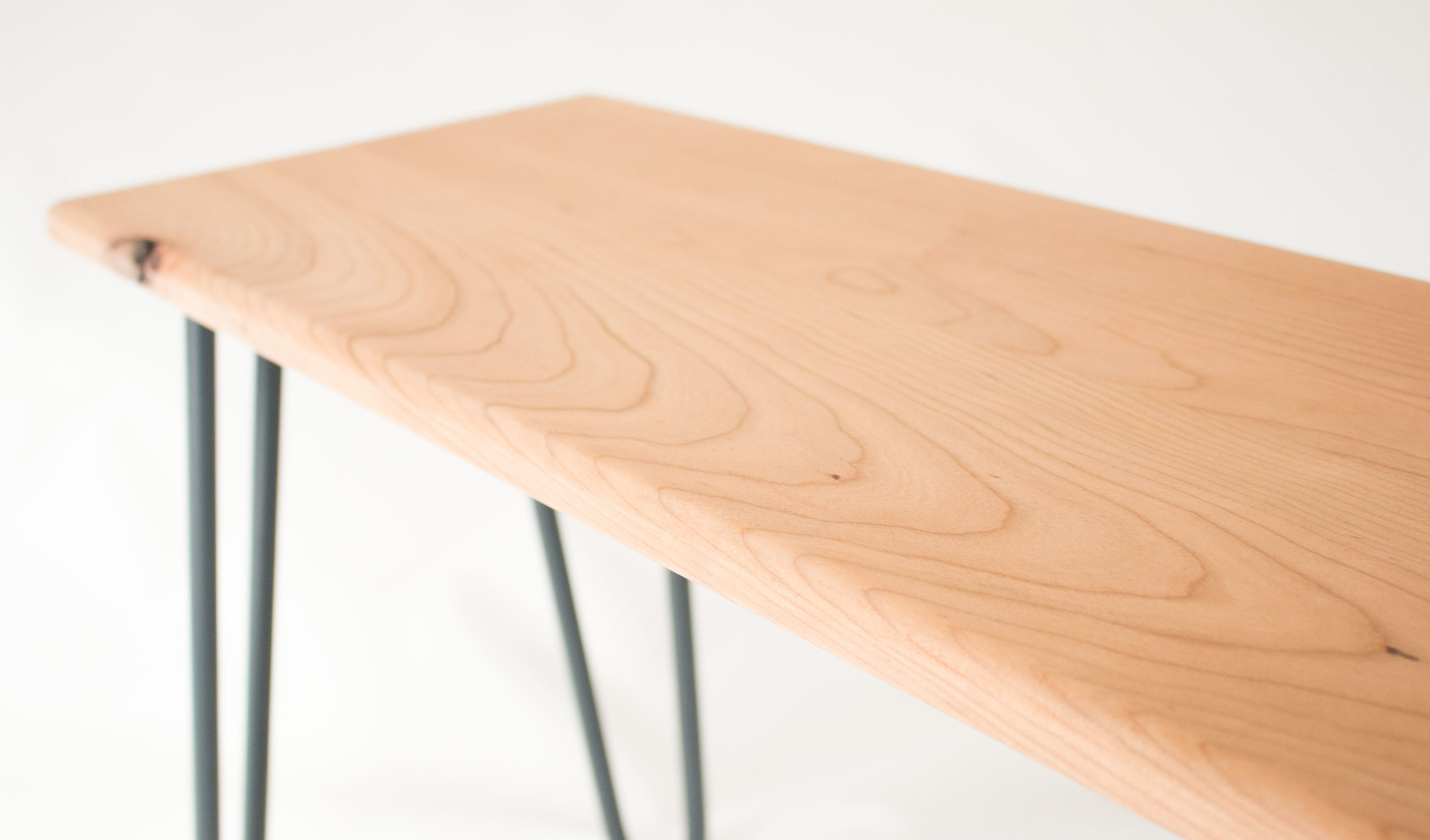 Cherry wood bench by Cord Industries, shown with lacquered steel hairpin legs.