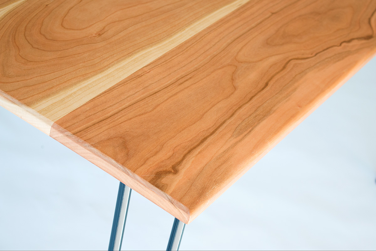 Cherry wood dining table by Cord Industries, shown with lacquered steel hairpin legs.
