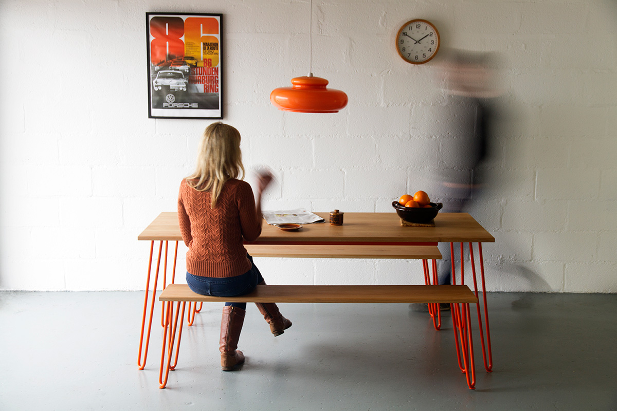Cord Industries hairpin leg dining set in oak with orange legs.