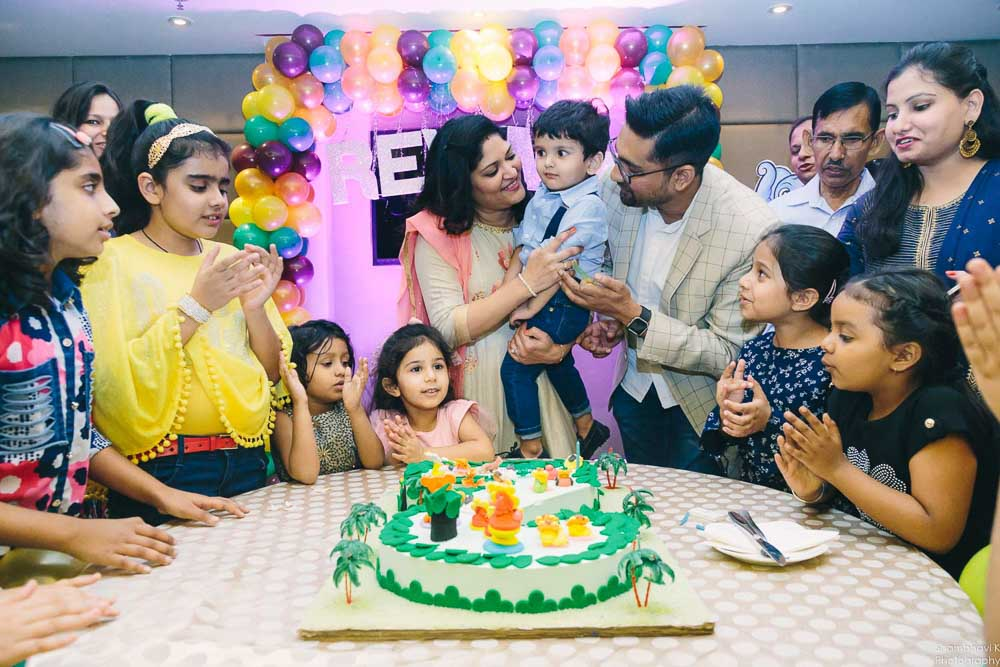 candid moments of birthday boy at cake cutting