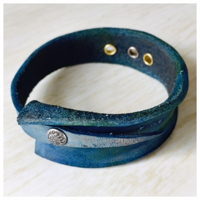 Secured, teal-dyed leather bangle with brass and nickle eyelets and riveted closure.