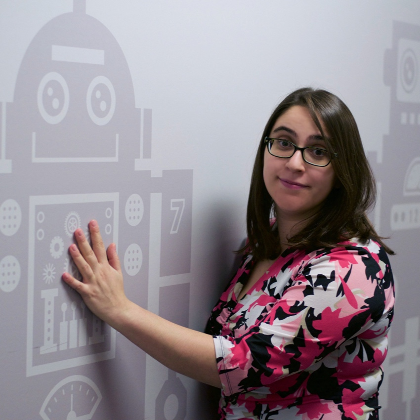 """Naomi Fitter escaped from Ohio at the age of 22. Her soothing midwestern voice has been described as """"sexy,"""" """"librarian-like,"""" and """"nearly inaudible."""" When she's not telling jokes, she spends her time studying robots."""