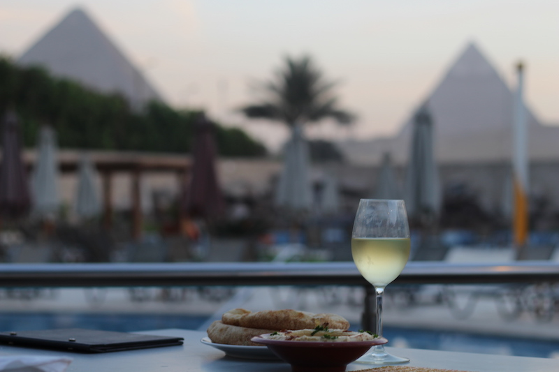 Having a poolside drink at the Le Meridien Pyramids Hotel with a perfect view of the Pyramids of Giza