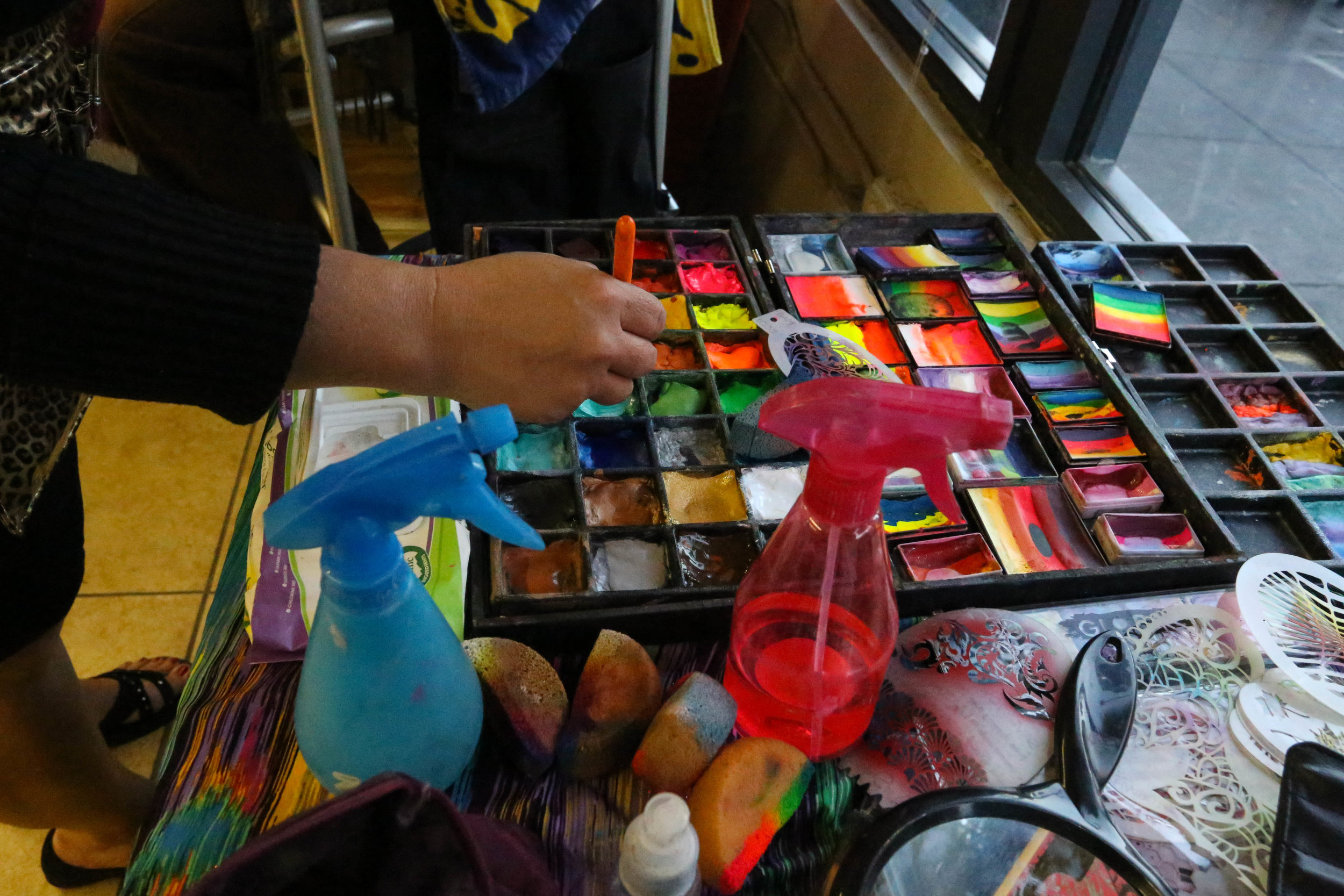 Jackie York, Make-up Your Mind, selects colors for her face painting design at the Sixth Street Community Room for 2 Blocks of Art walk.Friday, September 16, 2016.Mid-Market News