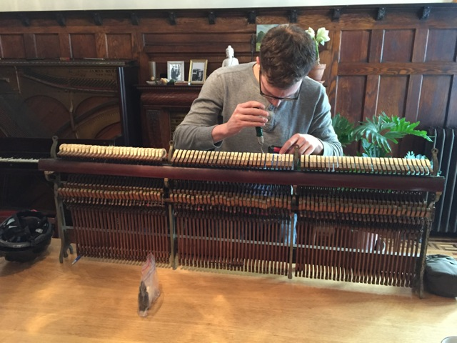 Registered Piano Technician Isaac Wynn works on an upright piano action.