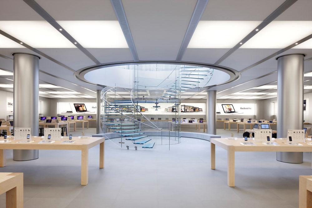 Agencement de la boutique Apple. Apple utilise beaucoup de lumière blanche et met en avant ses produits en laissant un espace entre chaque. On retrouve également l'image des produits dans le style clair et épuré de la boutique.