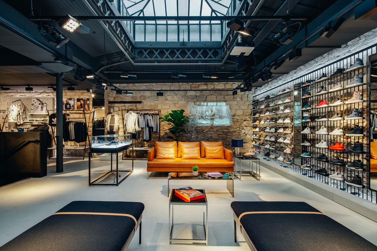 """La Boutique phare de """"Adidas Originals"""" à Paris. L'espace entre les produits est agencé par la mise en place d'un espace confortable qui permet aux clients de se sentir bien accueillis."""