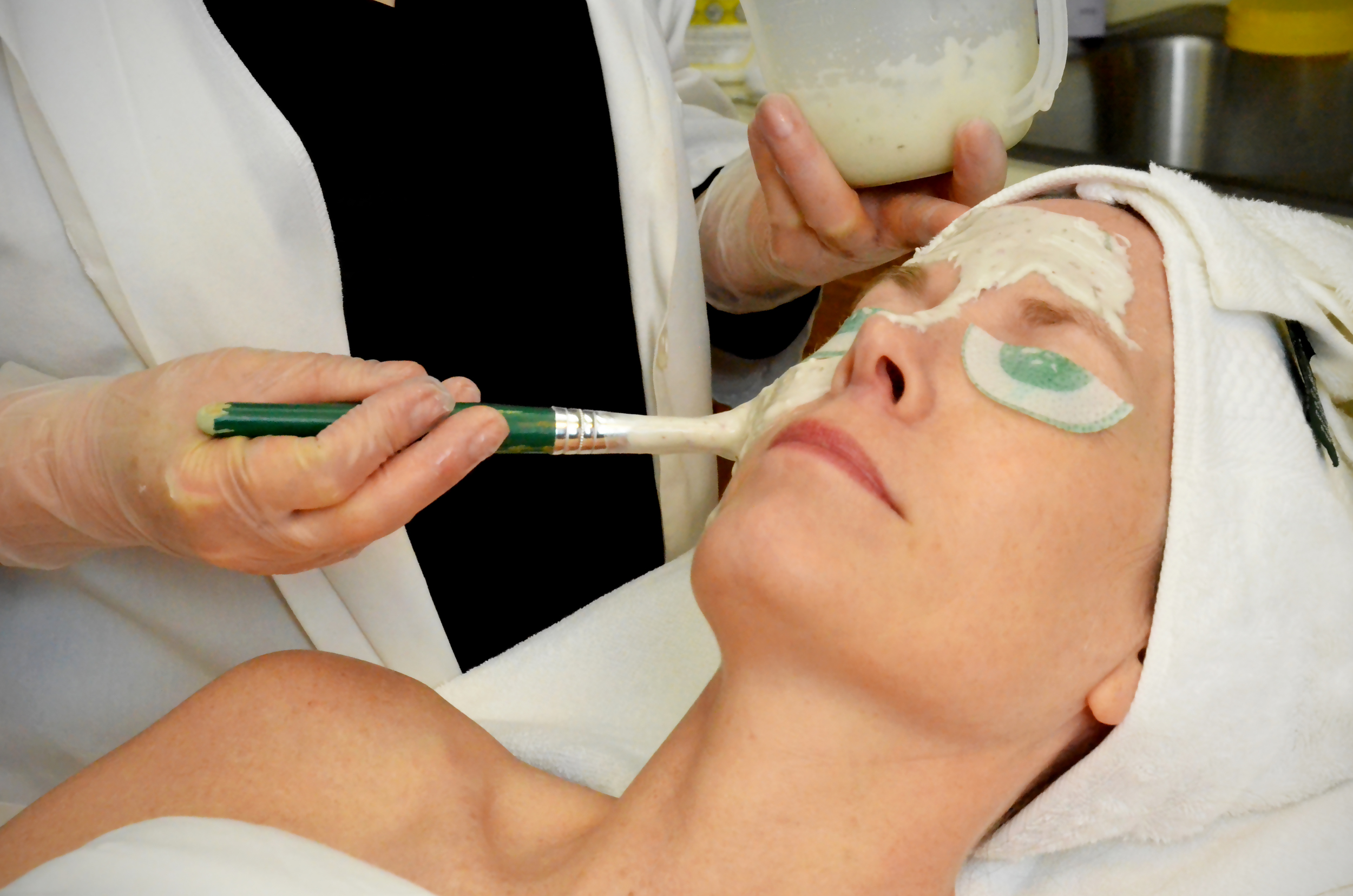 Teresa applies a mask for a client during a relaxing facial