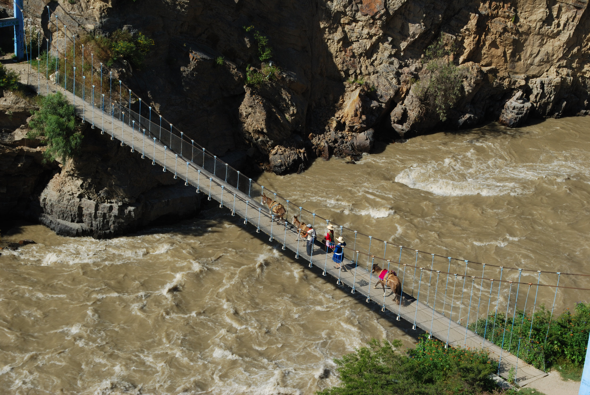 Suspension bridge across the fast-flowing Santa River being used by local farmers.