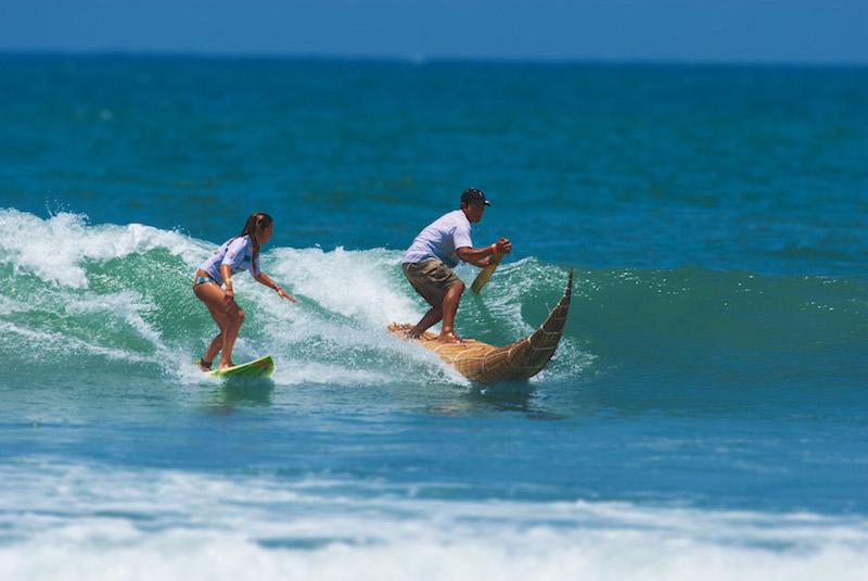 Surfer and  caballito  paddler riding the same wave at Huanchaco.