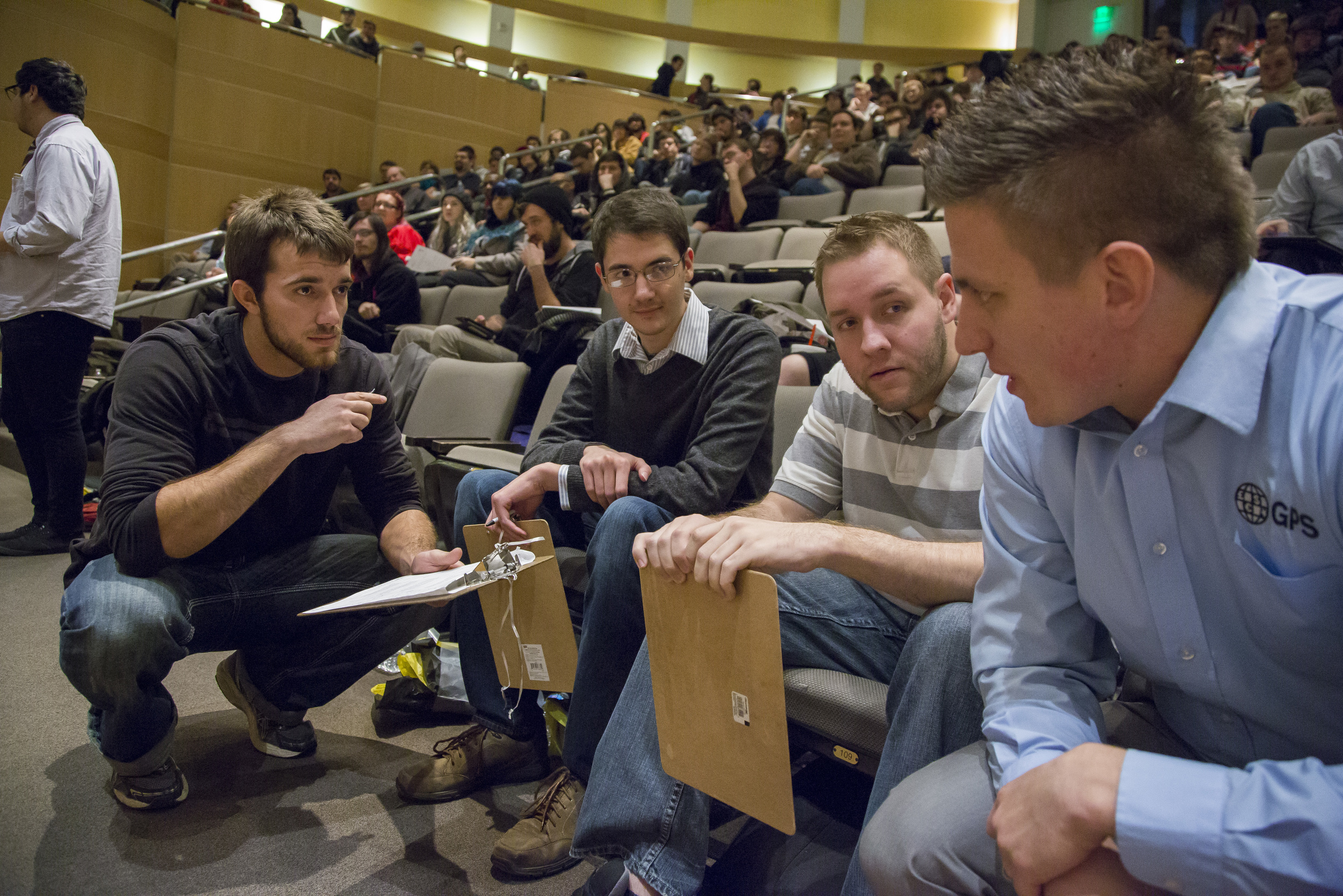 Kevin (center) and other alums judge current student projects at the 2015 December Capstone Project Invitational.
