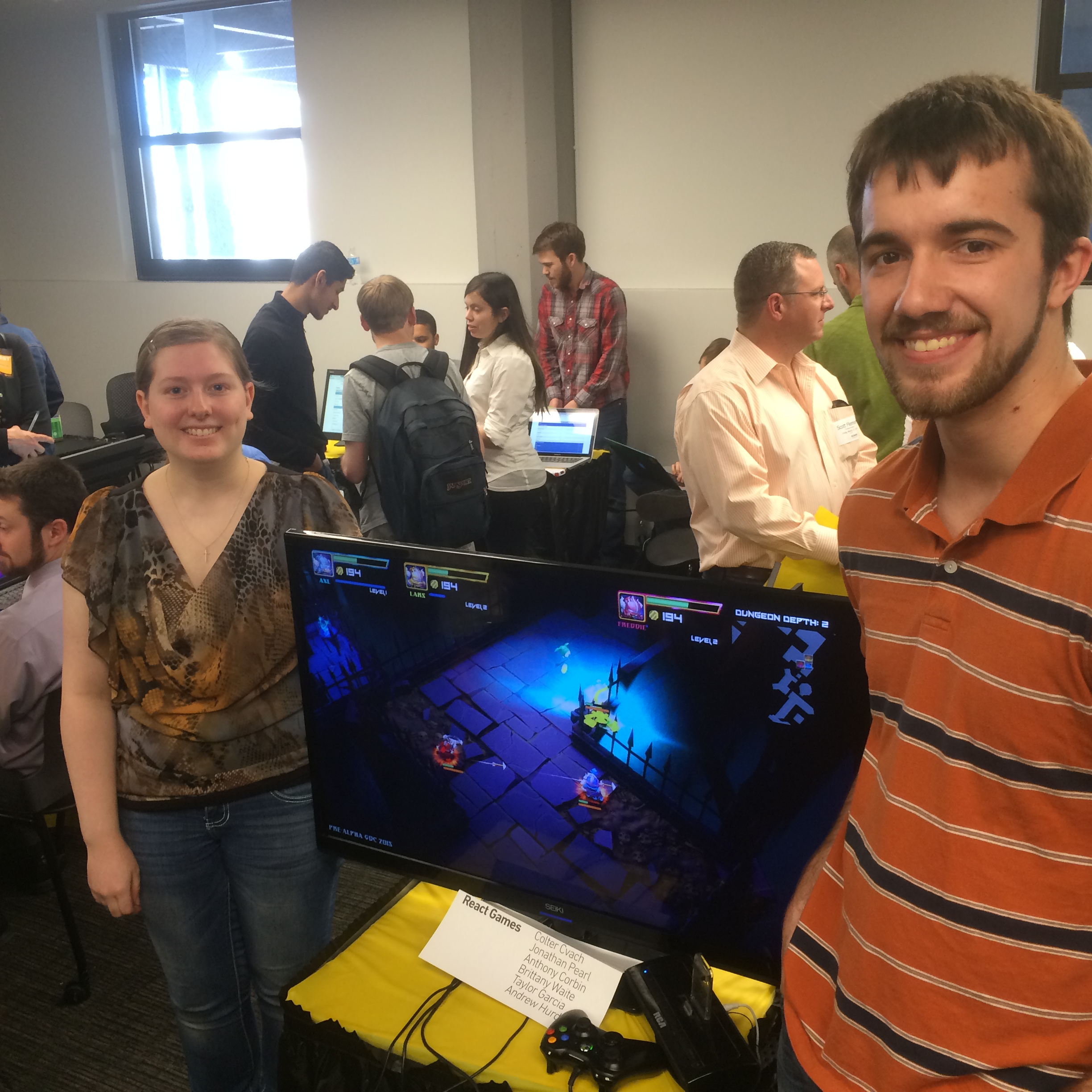 """Students show off """"Super Dungeon Bros."""" a game they assisted in developing with React Games at Project Showcase."""