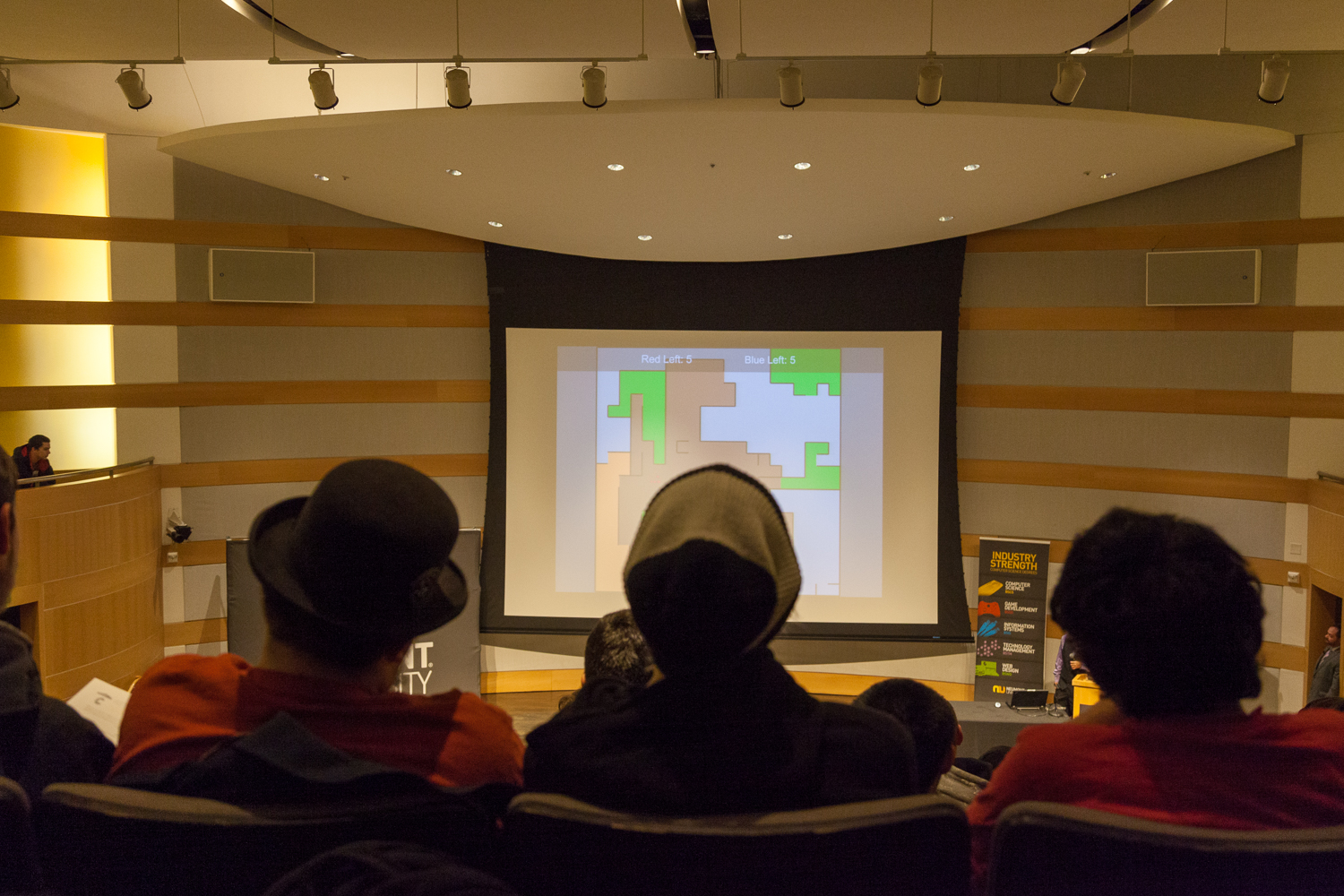 A student presents a game he developed at Neumont University's Capstone Project Invitational.