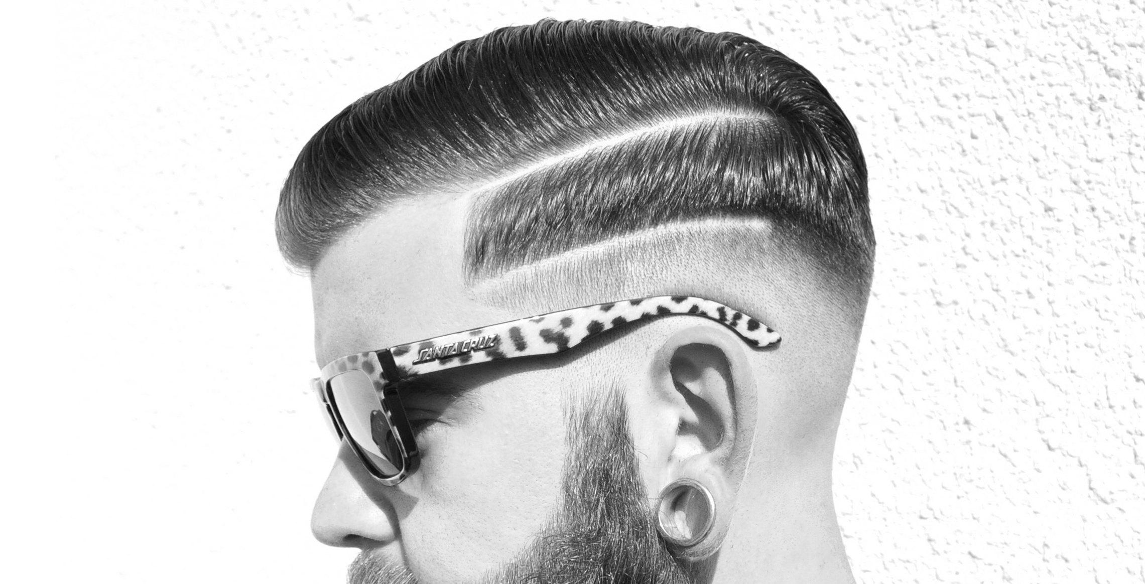 Hard line skin fade, styled with pomade.