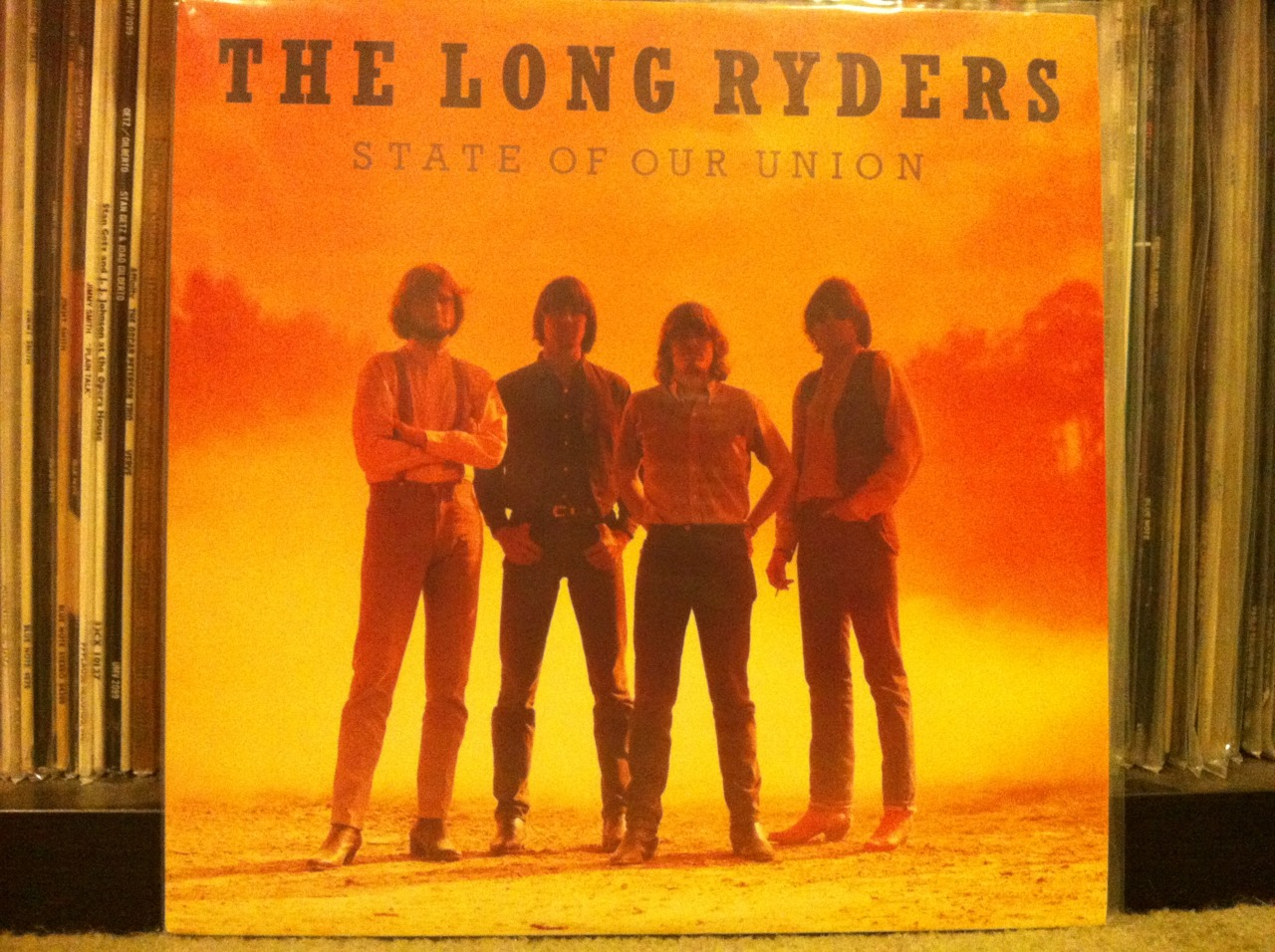 """The State Of Our Union!    """"I thought I saw some diplomat hawking secret plans in the park.   I thought I saw my president walking through Harlem late after dark.""""   Those first lines of this record's opener - Looking For Lewis And Clark - suggest you're in for a politically charged wild ride. Turns out it's a well-written, tuneful, fun one at that. I love this record for so many reasons and one of them is that The Long Ryders use this record to prove the supposed rock 'n' roll dust bowl of the 1980s is a myth.   This record is an appropriately arrogant blend of country rock love of Gram Parsons, plugged into some Byrdsian jangle guitar, a strong pop sensibility and the spiritof Woody Guthrie. And it all happened in 1985.   Sid Griffin (g), Stephen McCarthy (g), Greg Sowders (d), and Tom Stevens (b)came together again in 1985 to create this long-player filled withaddictive Americana (no wonder it was so popular in England!). It's their second record together with thisline-up. The first being 1984's Native Sons (which may have even more goingfor it). The same line-up minus bassist Tom Stevens put out a great EP in 1983called 10-5-60.   State Of Our Union is packed to the gills with some predictable stuff like weaving, bashing, jangly guitars. But, it's just as heavy into harmonica, autoharp, banjo, and lap steel. Oh, and drums that never miss a beat and keyboards that don't stink.   Funny thing is, State Of Our Union seems as well suited to the have/have not times of today as it did in the mid 80s. Or, in the 1930s for that matter. I'm not saying the record is timeless but man is it close. There's no doubt the band didn't like trickle down economics or Ronald Reagan's view of America. But to say the record is singularly focused on politics underestimates this slab of fine wax. It's as easy to pump your fist in the air in support of the small man as it is to get lost in the scenery of riding the rails and filling up your coupe with gas from a glass topper. It's simple"""