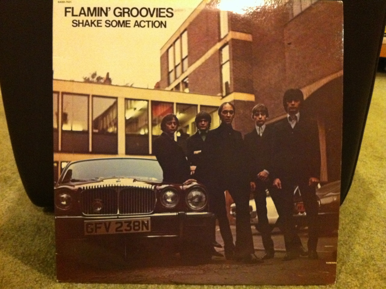 "Bust Out At Full Speed!!!    The Flamin' Groovies are one of the most awesome (if slightly confusing) bands ever! I'll cover the confusion in the  For Weirdos Only  section below. This long-player - Shake Some Action - is my favorite Flamin' Groovies album. Of the second era. This is the Cyril Jordan led version of the band with Chris Wilson singing vocals. It sounds real treble-y and jangle-y and super rocking. To my ears it sounds like The Beatles married Bob Dylan and gave birth to their baby - the Flamin' Groovies - on a flamin' red Rickenbacker 12 string electric guitar.    Every time I listen to this album it takes me back to junior high. I remember gambling on this album because it looked so cool and it was on the Sire label. I loved the Ramones and the Talking Heads at the time and they were on Sire so I thought these Flamin' Groovies had promise. And promise they did. They promised to kick me in the arse with every listen. They rocked hard and there's not a weak song on this record. Not one.   There's only one weak thing about this album in my opinion. It sounds like it was recorded beneath a million cotton balls inside a gauze wrapped cocoon of felt. Maybe I'm exaggerating. This is one of very few instances where I think the recent Rhino UK collection ""Flamin' Groovies At Full Speed: The Complete Sire Recordings"" sounds better on compact disc. If you know me, then you know I love the sound of wax. Vinyl. The LP. The rekkid. But this one sounds better on this new CD collection.    Flamin' Groovies At Full Speed: The Complete Sire Recordings is a great deal because it sounds awesome, you get some unreleased and rare tracks and if you don't buy it you'll be making a huge mistake. It contains all three of their mind-blowing Sire records - Shake Some Action, Flamin' Groovies Now and Jumpin' In The Night. Trust me. They're awesome. Three slabs of wax on two compact discs. Do it!   In large part, I credit the Flamin' Groovies with getting me interested in a band I'll cover in much detail later - The Beatles.      For Weirdos Only:   Shake Some Action came out in 1976. It was their first new LP of new music since 1971's Teenage Head (my favorite album of the 1st era). Shake Some Action's sound is nothing like that of the first era Flamin' Groovies. That band had a harder Stones-y rockabilly edge that was amazing in it's way. I happen to love both eras - the Roy Loney/Cyril Jordan led first era  and  the Cyril Jordan/Chris Wilson led second era.    For Weirdos Only (part 2):   If you look closely, you can see a small (¾"") horizontal slice in the album jacket at bottom right. Cheapskate rock 'n' rollers will recognize this right away as a ""cut-out"" record. For the uninitiated, you could find bins and bins of these ""cut-out"" records at your local record store for between $1 - $4 or so back in the 70s and 80s. They were records that didn't sell well and were ""cut"" to render them identifiable as cut-outs and then sold cheap to get rid of them. That's how I found this record. Most likely next to a Fleetwood Mac Tusk album. Yuck.    Here's an audio-only sample from Shake Some Action:   http://www.youtube.com/watch?v=L2Y5LKZPwV4"