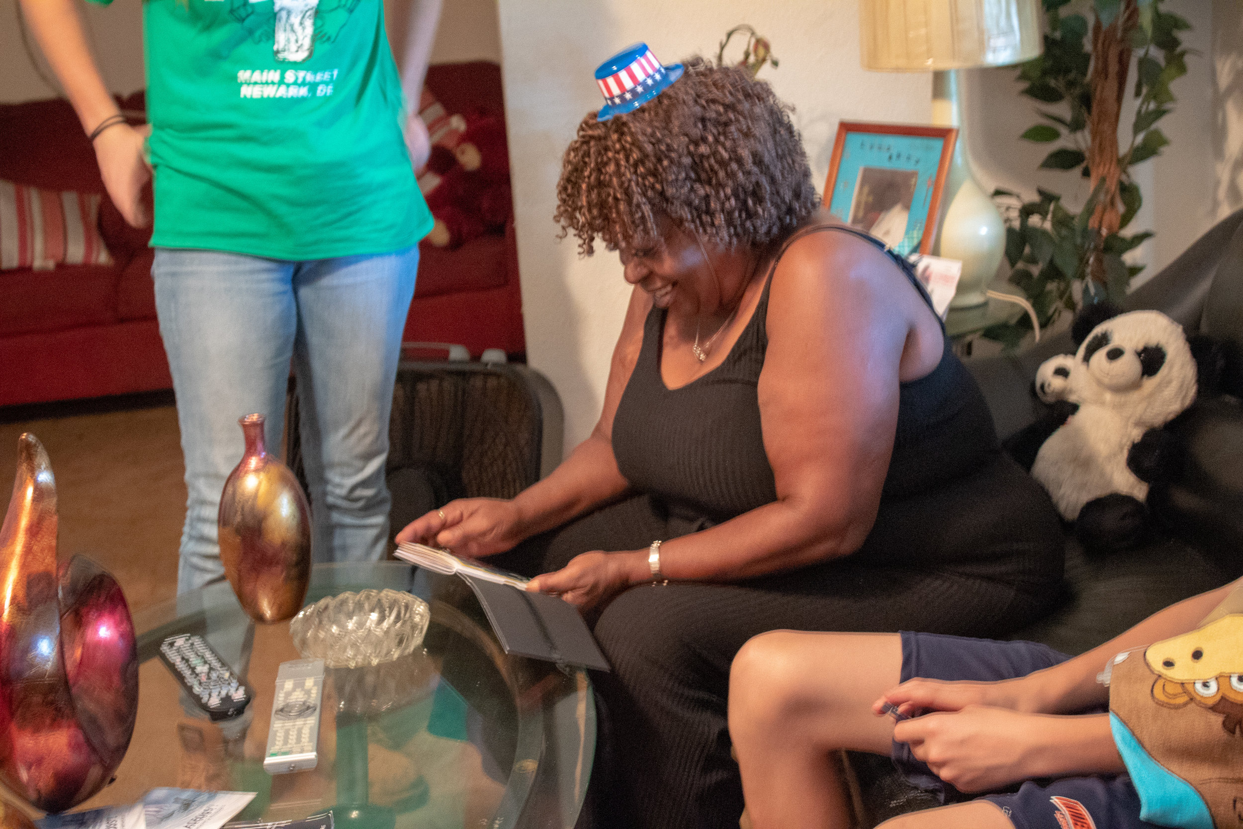 Mary Rodriguez, a Blueprint homeowner, receives her scrapbook from volunteers working on her home.