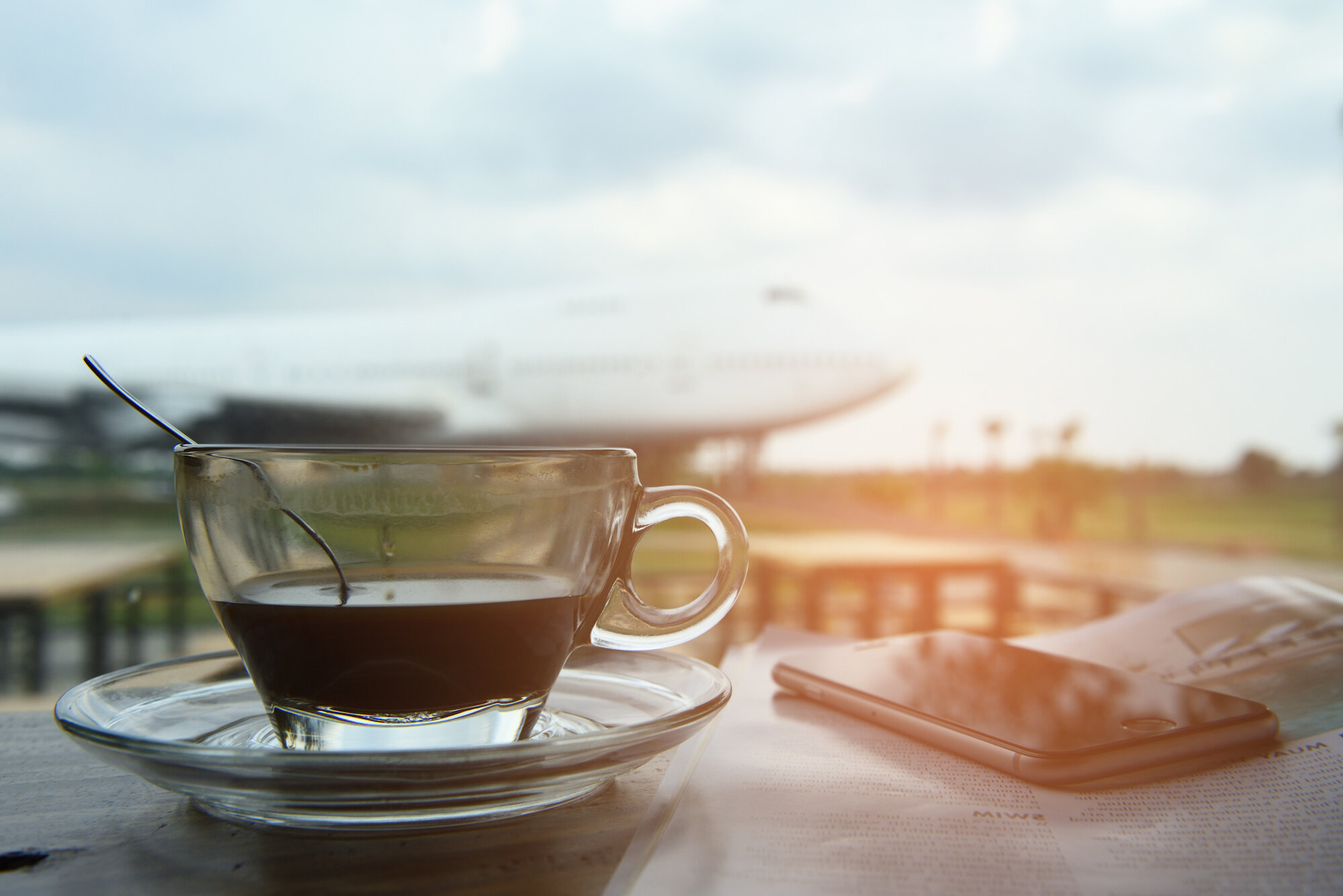 Black coffee and smartphone ,book is placed on the table at the private airport.