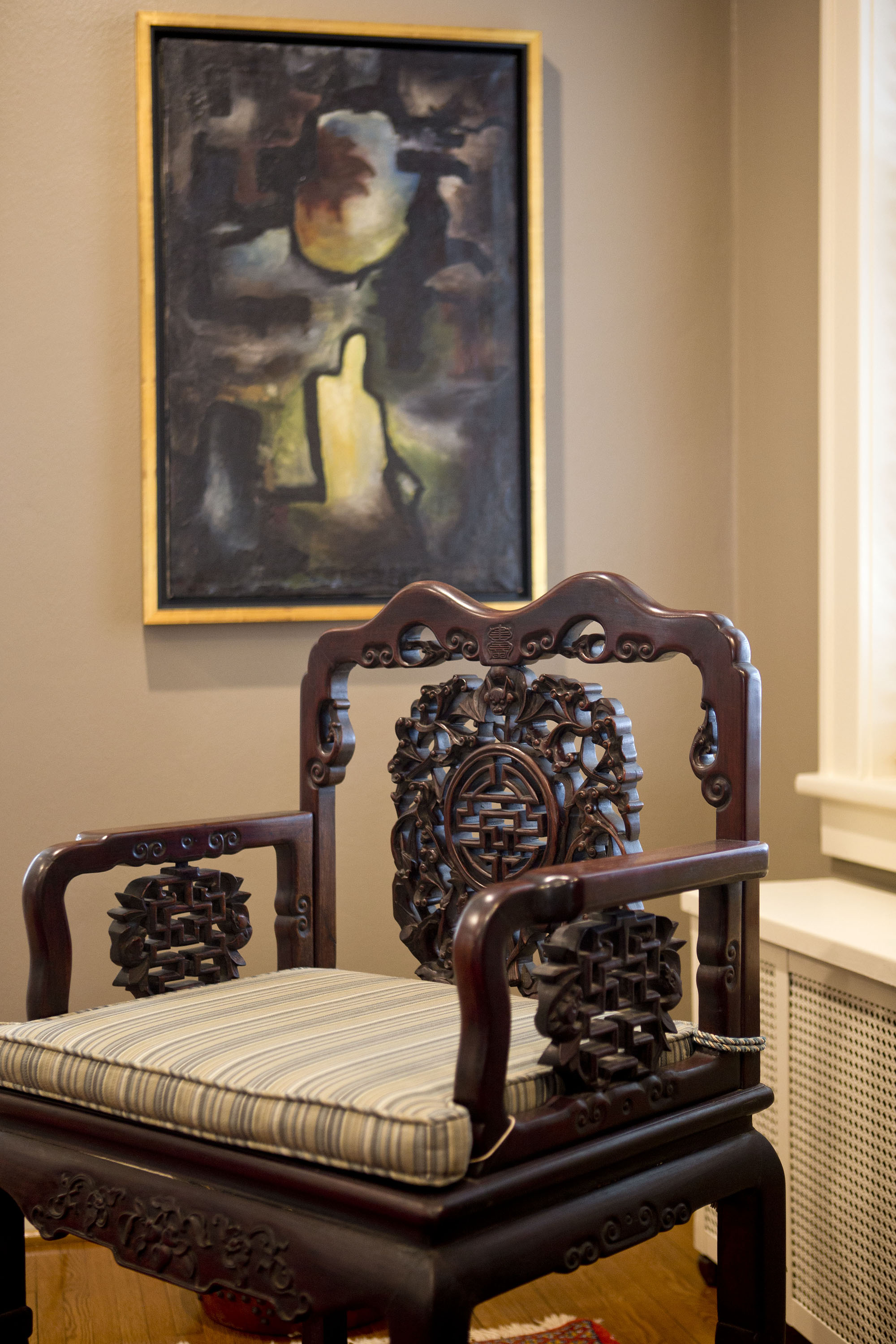 Modern art and an antique Chineese chair stands in the window-lit corner of the family room.