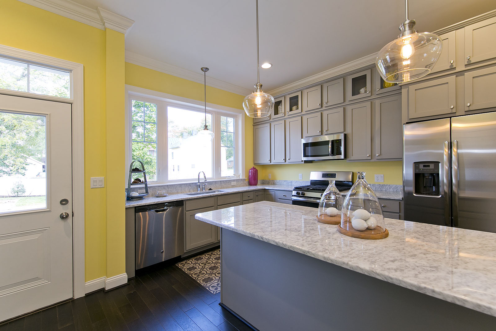 In this  kitchen , we doubled down on the sunniness of the space by balancing a light and cheerful yellow with bright white trim and medium greige cabinets.  Photo: Matthew Lofton