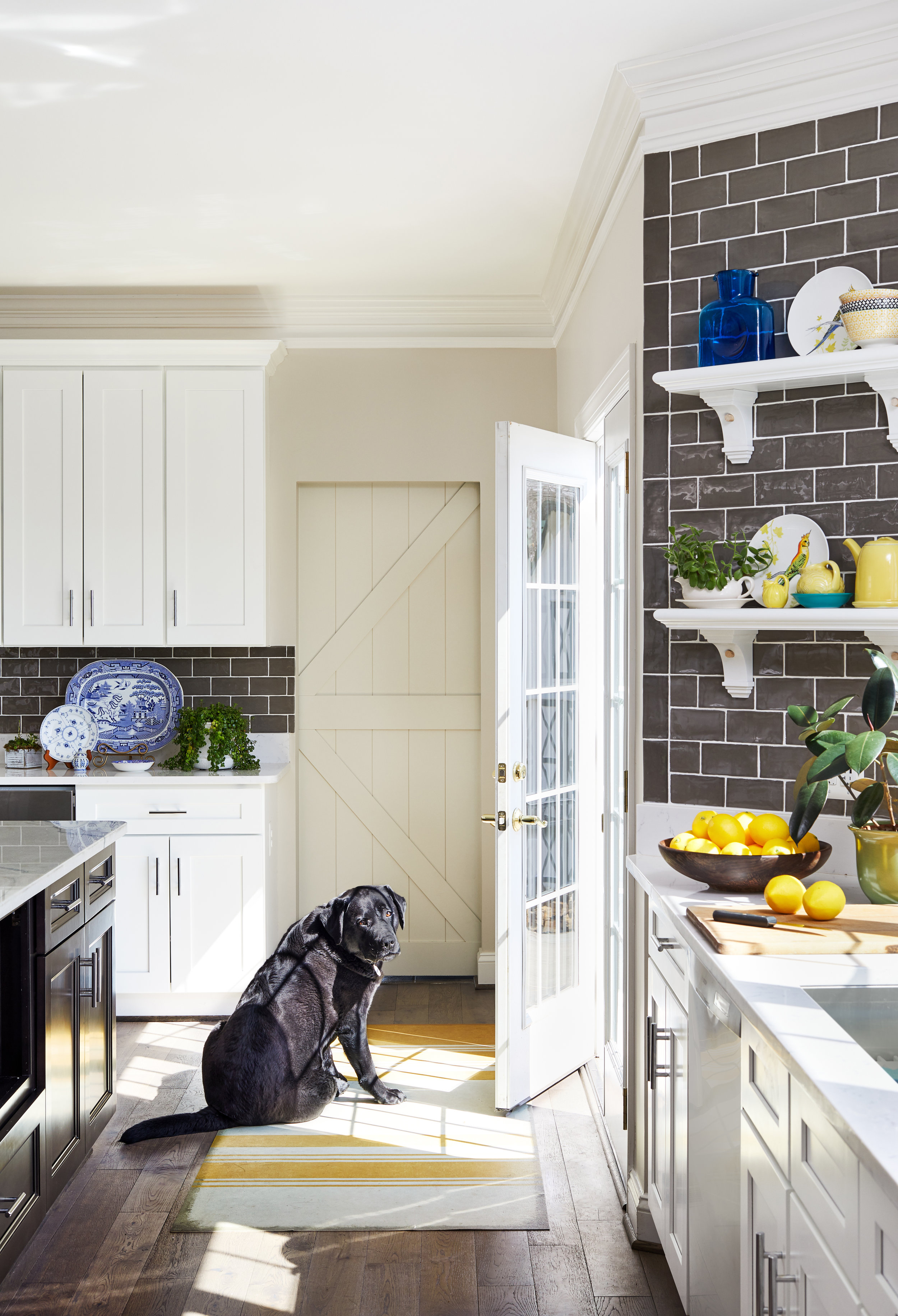 Fresh modern farmhouse country kitchen renovation. Gray and white kitchen with pops of yellow. Best tile for a backsplash. Vintage inspired floor mats make in America by Spicher & Co. Sunny glass back door off kitchen. Marble countertops. Photo by Stacy Zarin Goldberg.