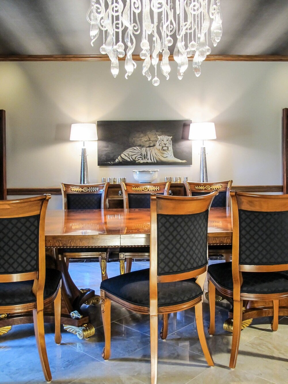 This dining room was made for drama and lengthy evening dinners. The dark, striated wallpaper on the ceiling invites guests to feel cocooned, cozy and to pour that second glass.