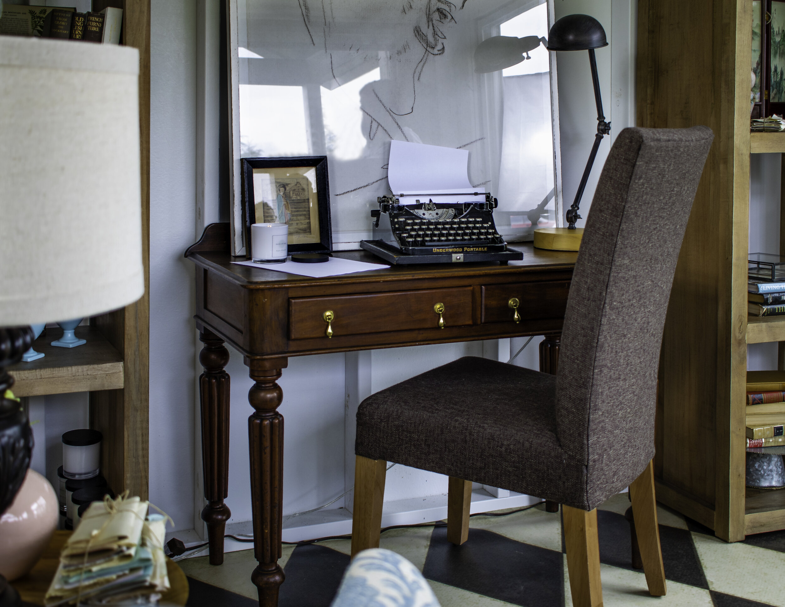An antique writer's desk fits perfectly on the back wall of the she shed.