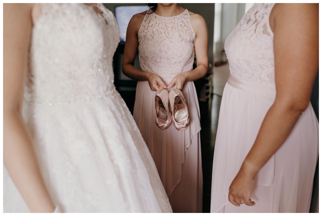 bridesmaid holding bride's shoes