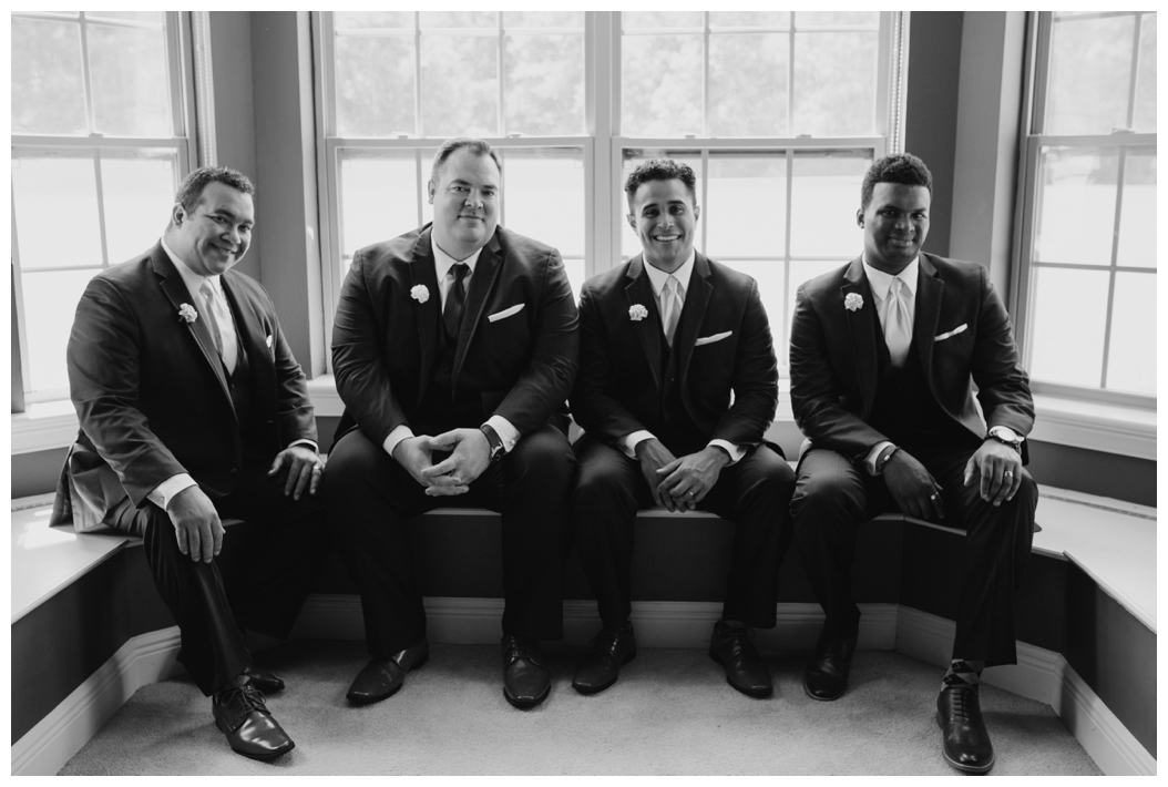 groom and his groomsmen sitting by the window