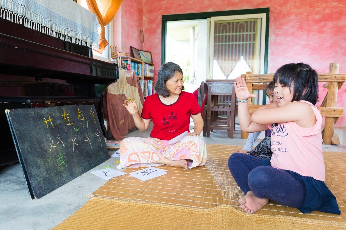 Founder of Tamorak, Nakaw, teaches Chinese characters to two elementary student using illustrations and body language.
