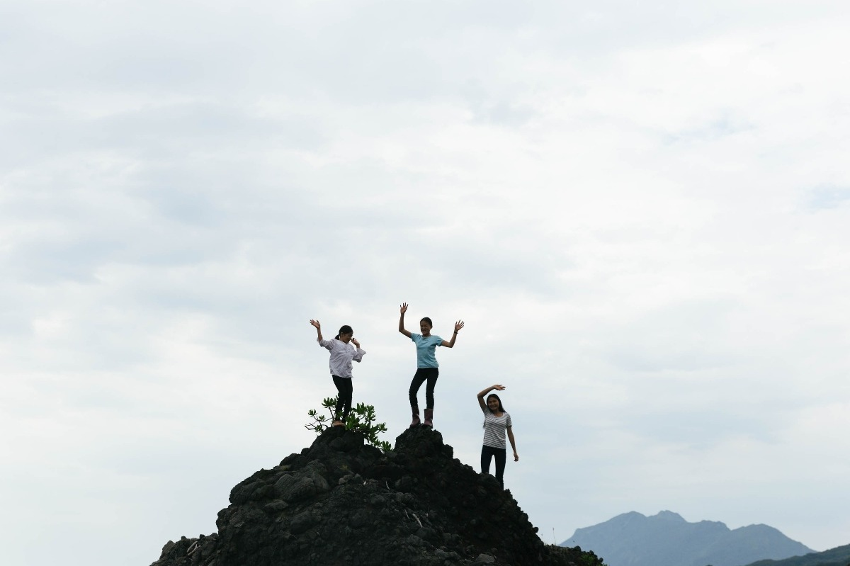 Poror, Arigfowang, and Atomo (Nakaw's three children) stand against the stunning landscape of east coast Taiwan located by the school.