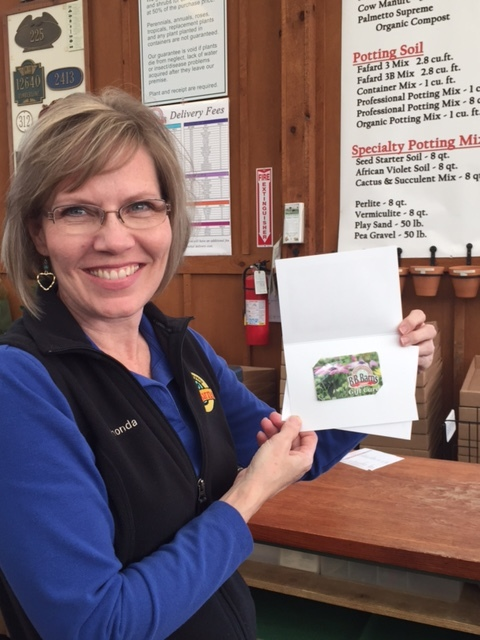 Rhonda holding what she wants, a gift card (for the practical gardener)