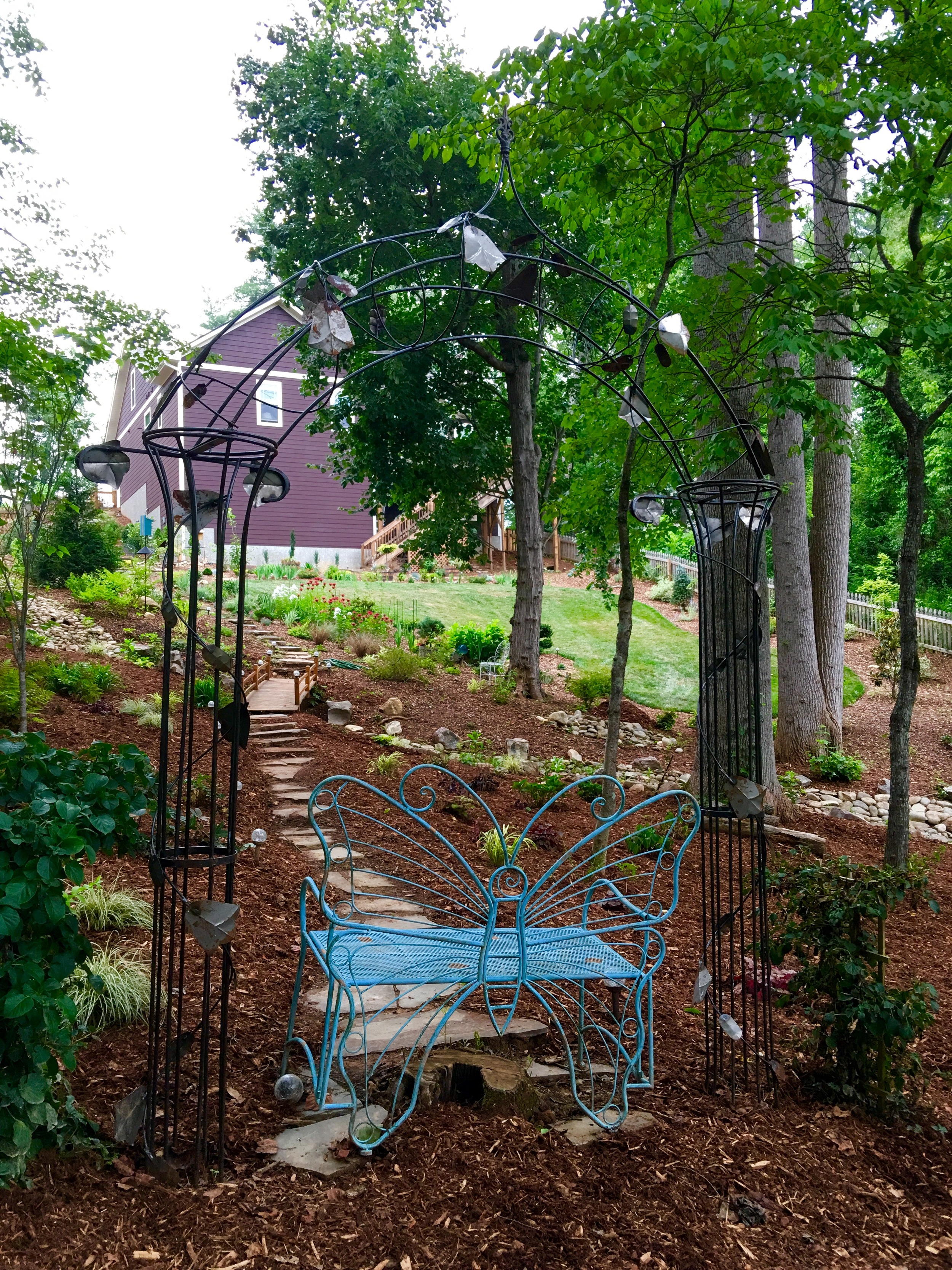 This secret garden is in memory of Becky's mom and sister, Rita. It is part of her shade garden and the trellis will be covered with climbing hydrangea in a few short years.