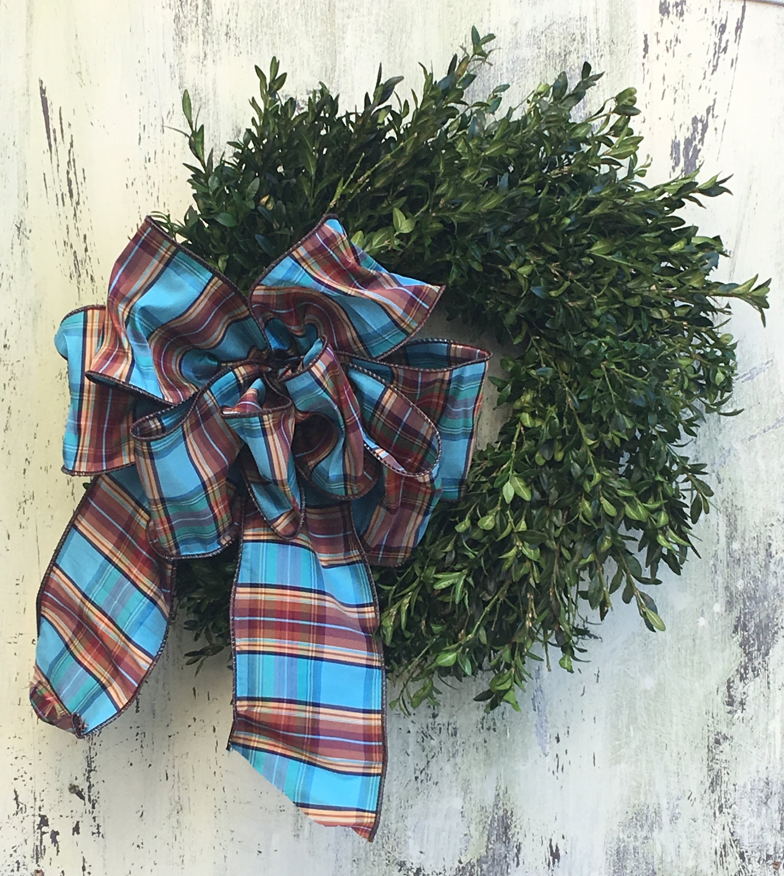 Traditional plaid bow on a boxwood wreath.