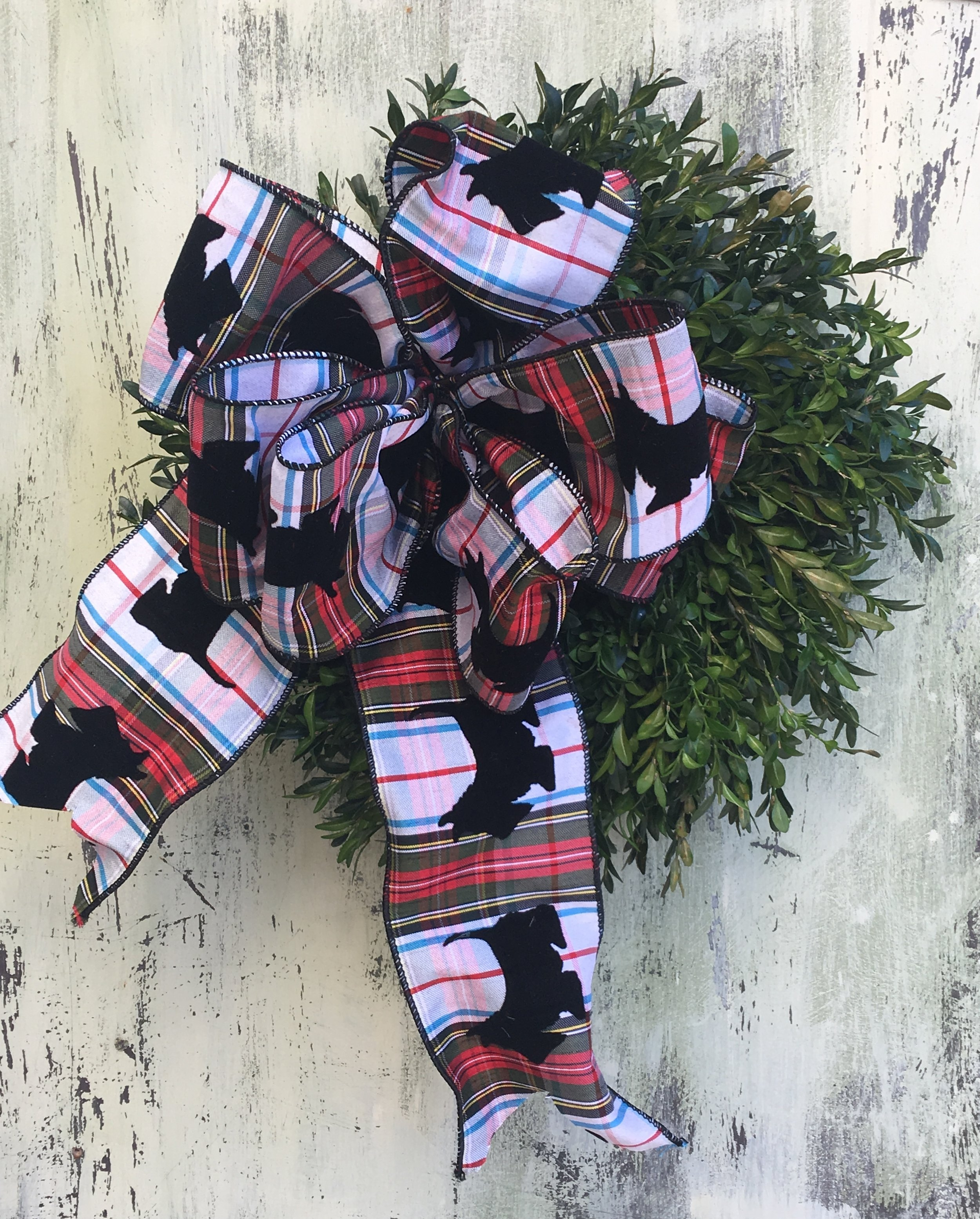 Love your pet? Express it in your holiday ribbon. Dog plaid ribbon on boxwood wreath.