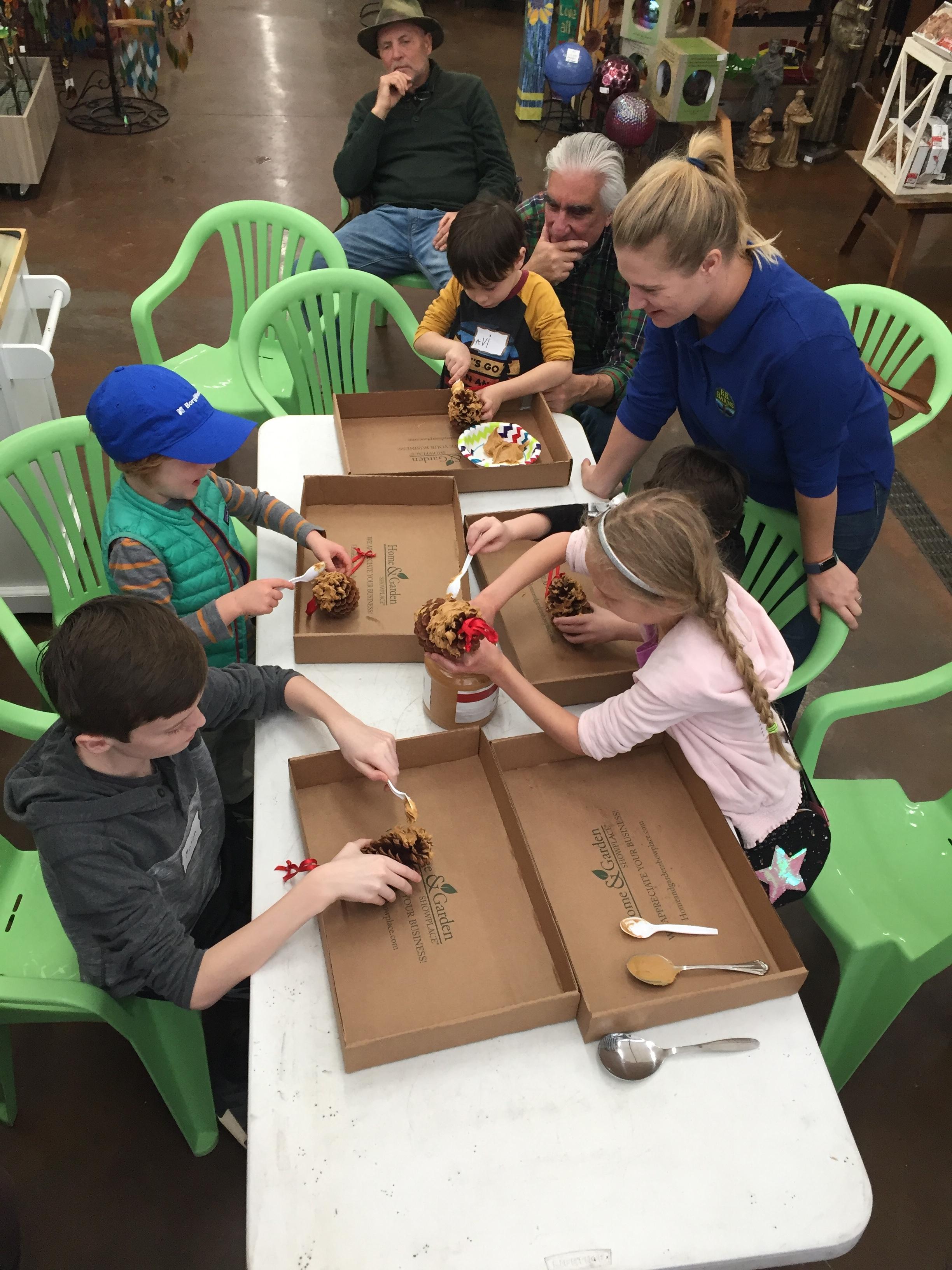Jenna Mace helping children in December make pine cone garlands for the birds.
