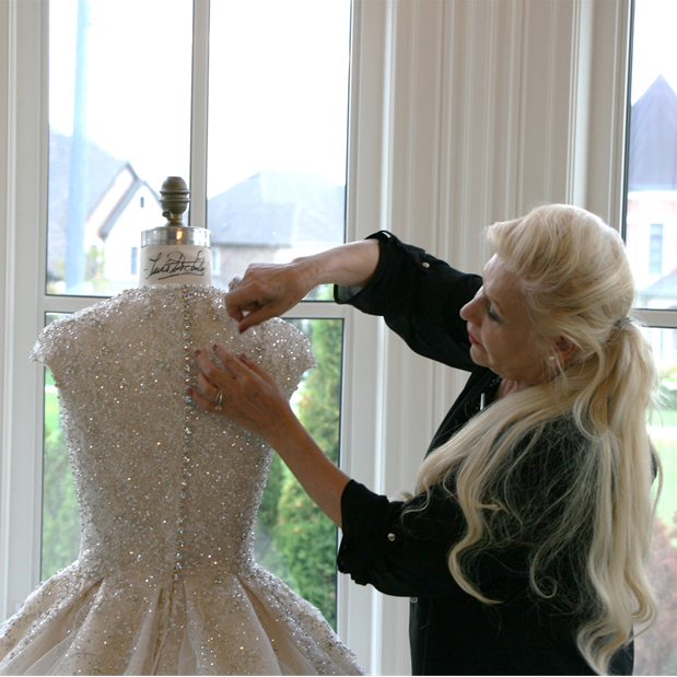 Photo of Ines di Santo perfecting a gown.