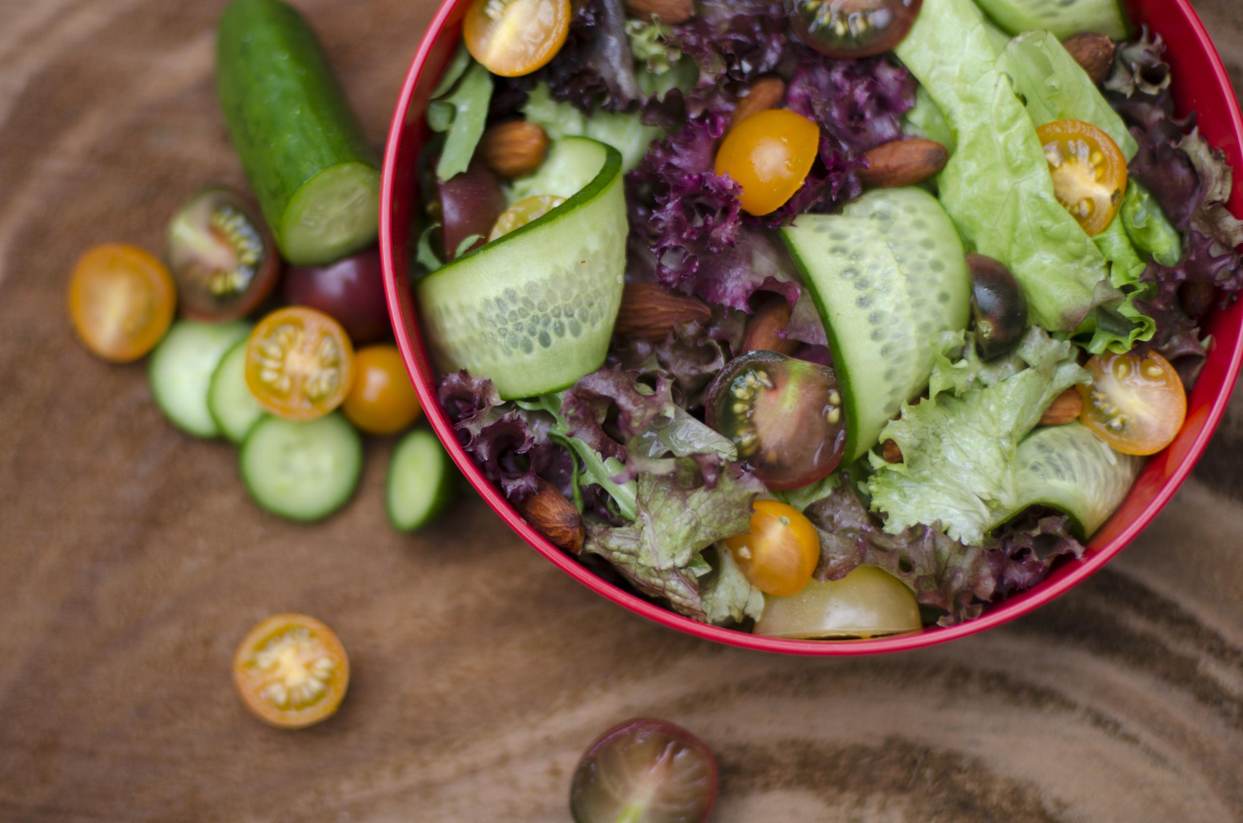 Ensalada de lechugas mixtas, almendras, tomates y pepinos miniatura y aderezo al gusto.