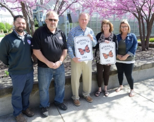 Members from Sandusky, Ohio pose with their Monarch City USA signs. Left to right: public services director Brad Link, commissioner Dave Waddington, ex officio mayor Dennis Murray Jr., Ontario Elementary School teacher Jacquelyn Betzel-Conrad and public services administrative assistant Kelly Kromer  Photo credit: Jilly Burns –  Sandusky Register