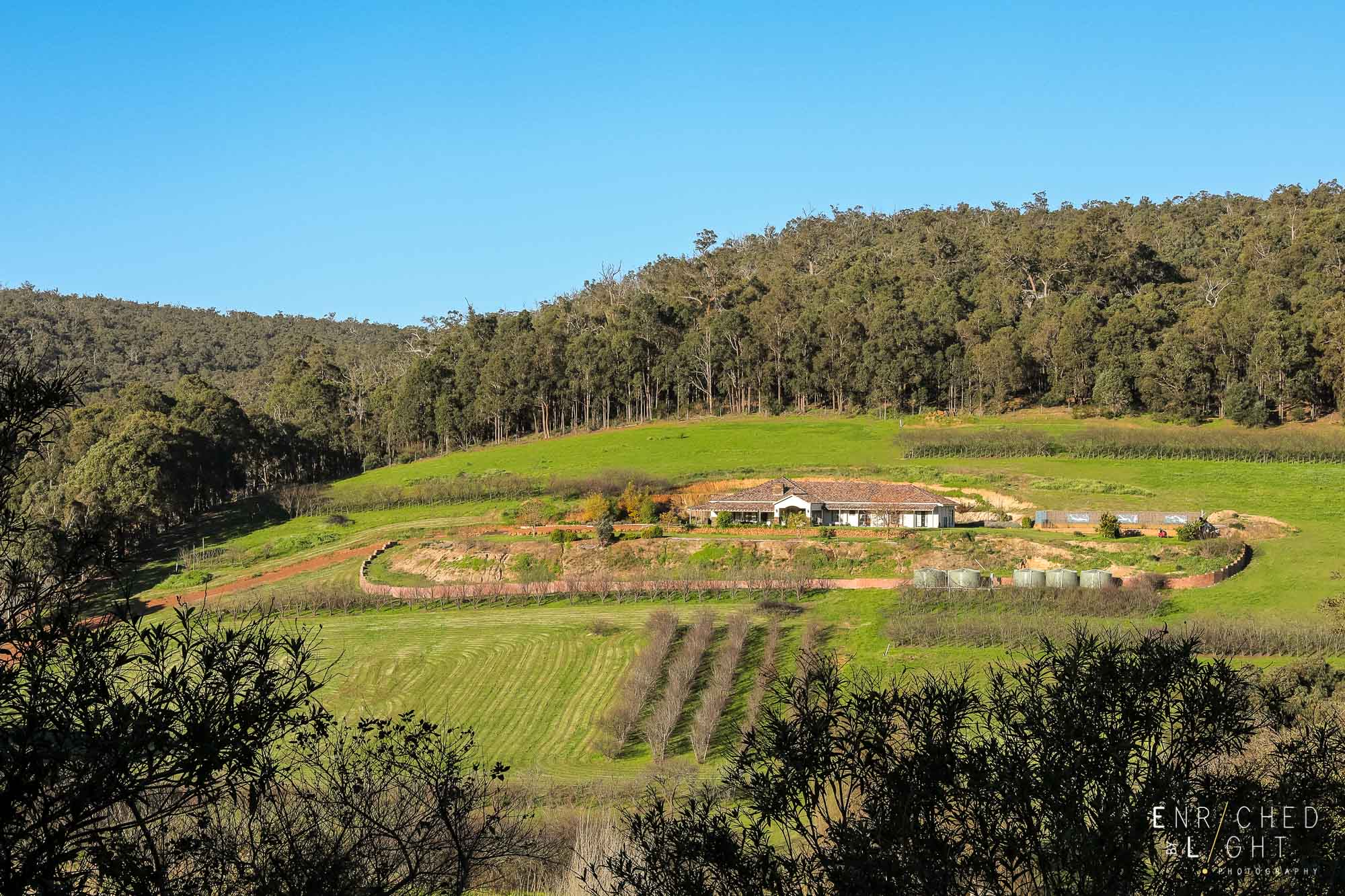 The rolling hills and elevated farmhouses and vineyards create the mood for a scenic drive.