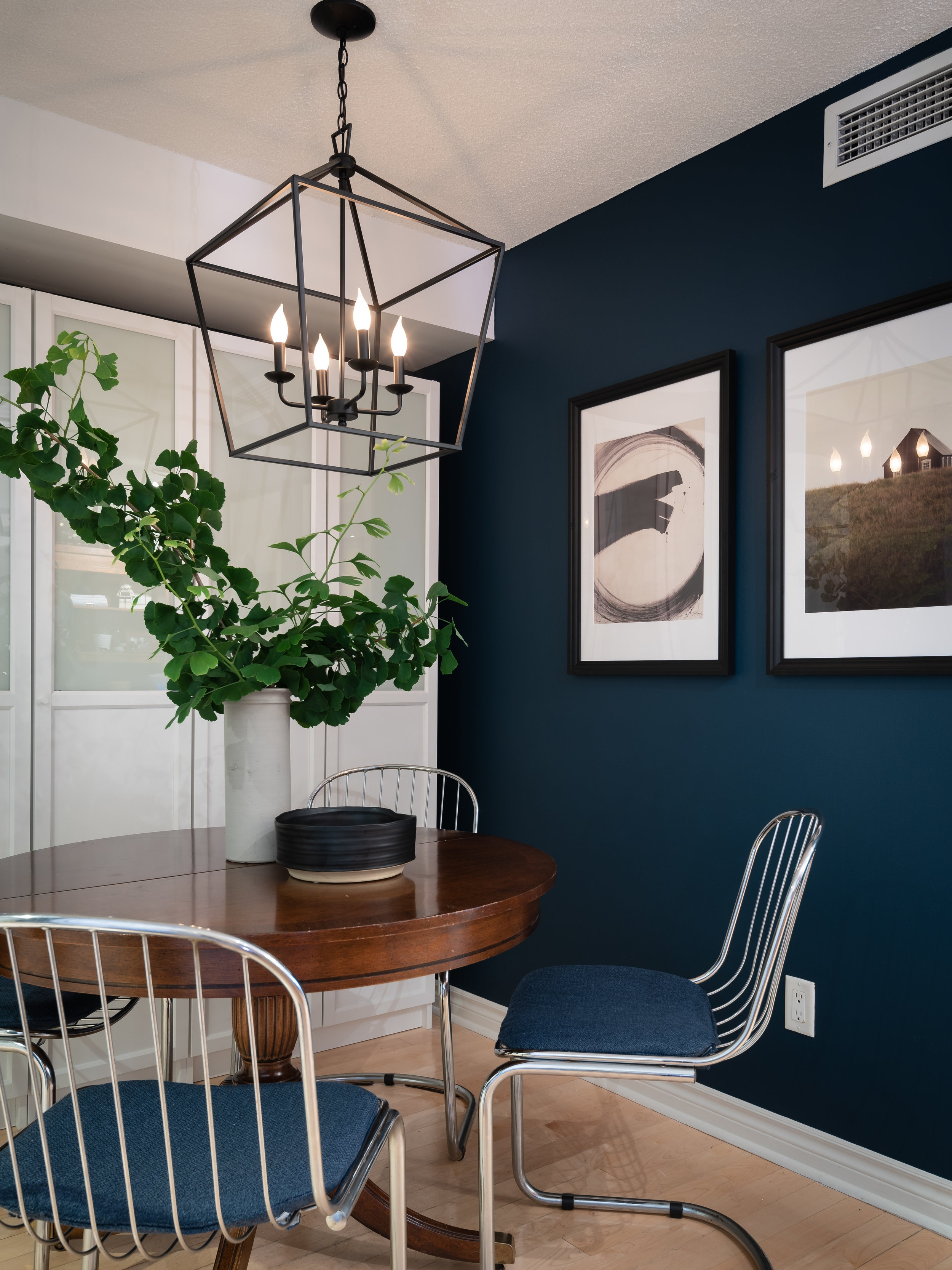In the new dining nook there's room for a smaller round table that can be extended and four dining chairs — plenty of seating for everyday dining. Joel had the cushions on the vintage chairs reupholstered in a navy blue to nod to the new wall colour. The homeowners ended up loving the blue walls so much that they painted their bathroom with the same colour!