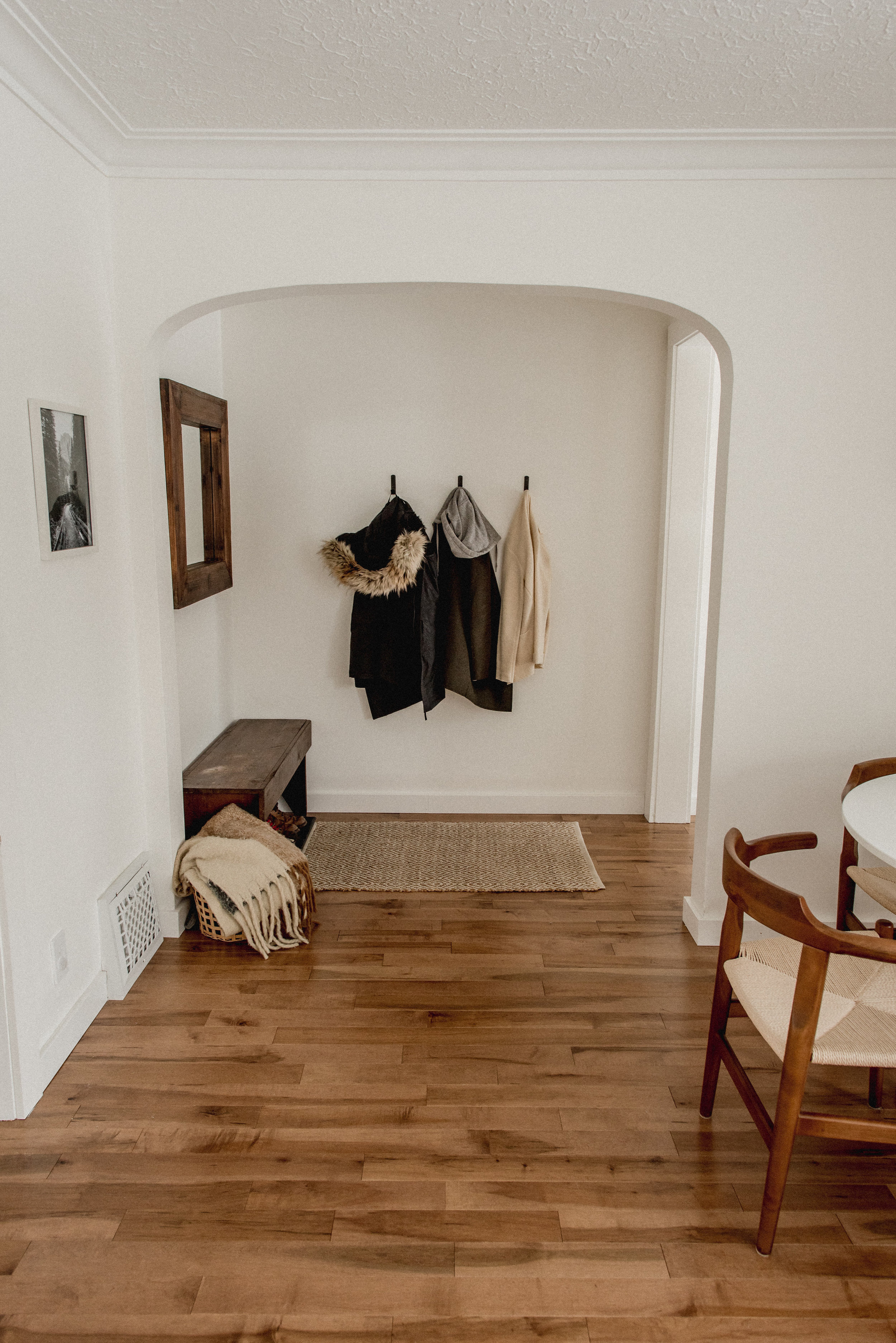 Simple and minimalist entrance way with bench and wall hooks