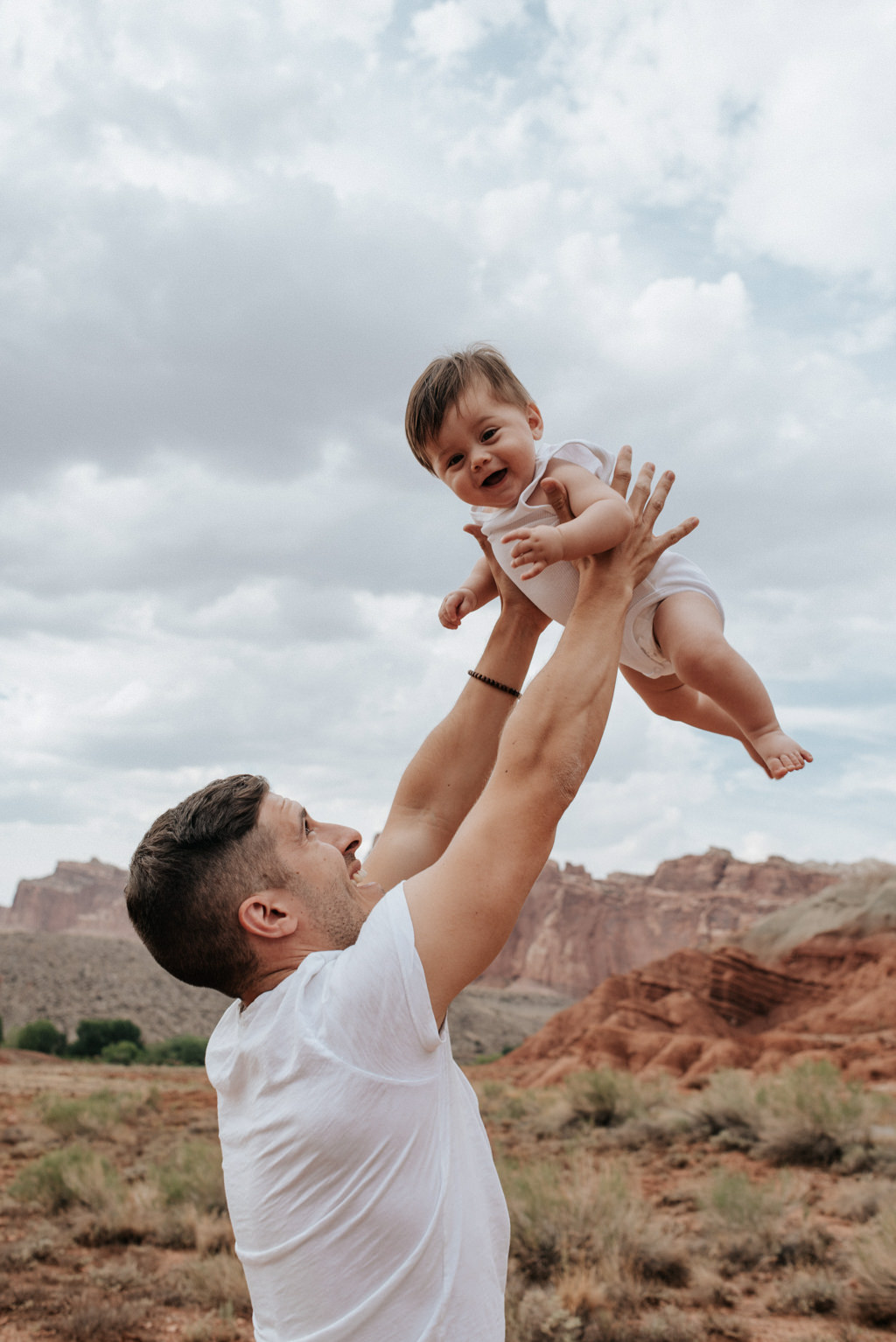 Father throwing baby son in air in Capitol Reef National Park