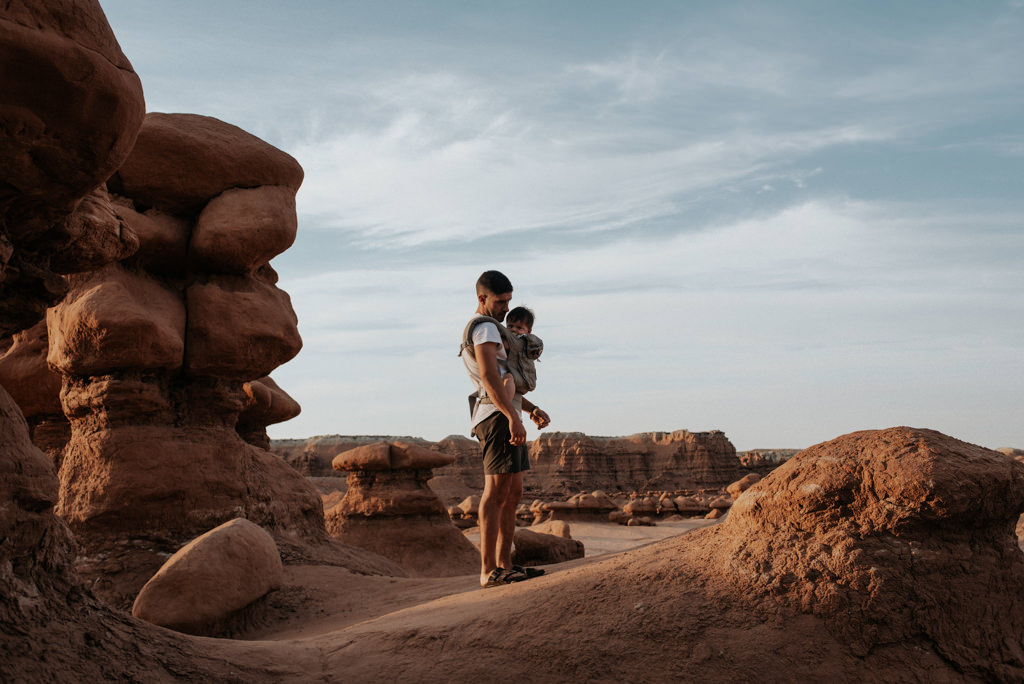 Father with infant son in carrier hiking at Goblin Valley State Park