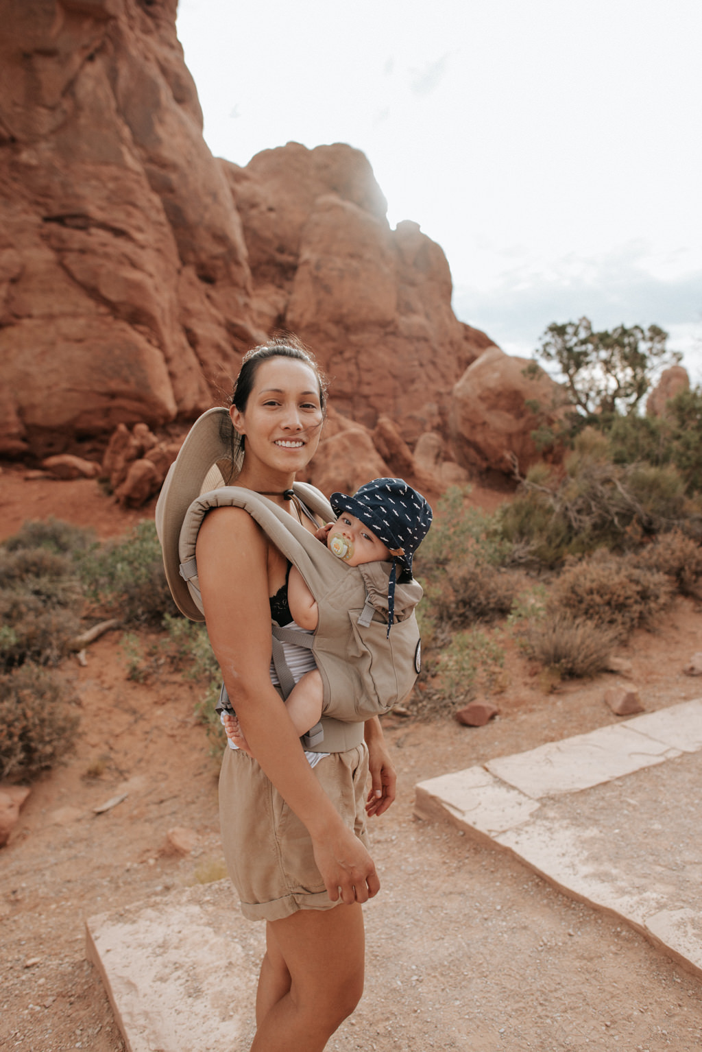 Young mother and infant son hiking in Arches National Park