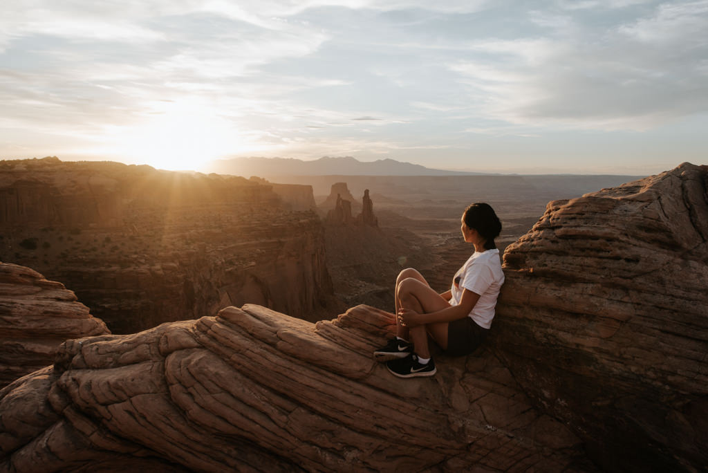 Woman watching sunrise at Mesa Arch in Canyonlands National Park