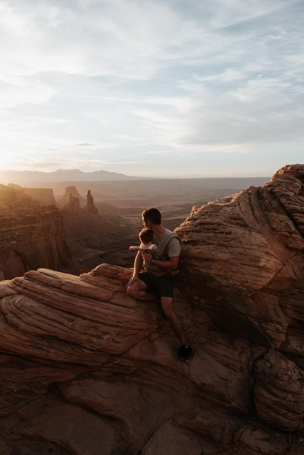 Man holding infant son and watching sunrise at Mesa Arch in Canyonlands National Park