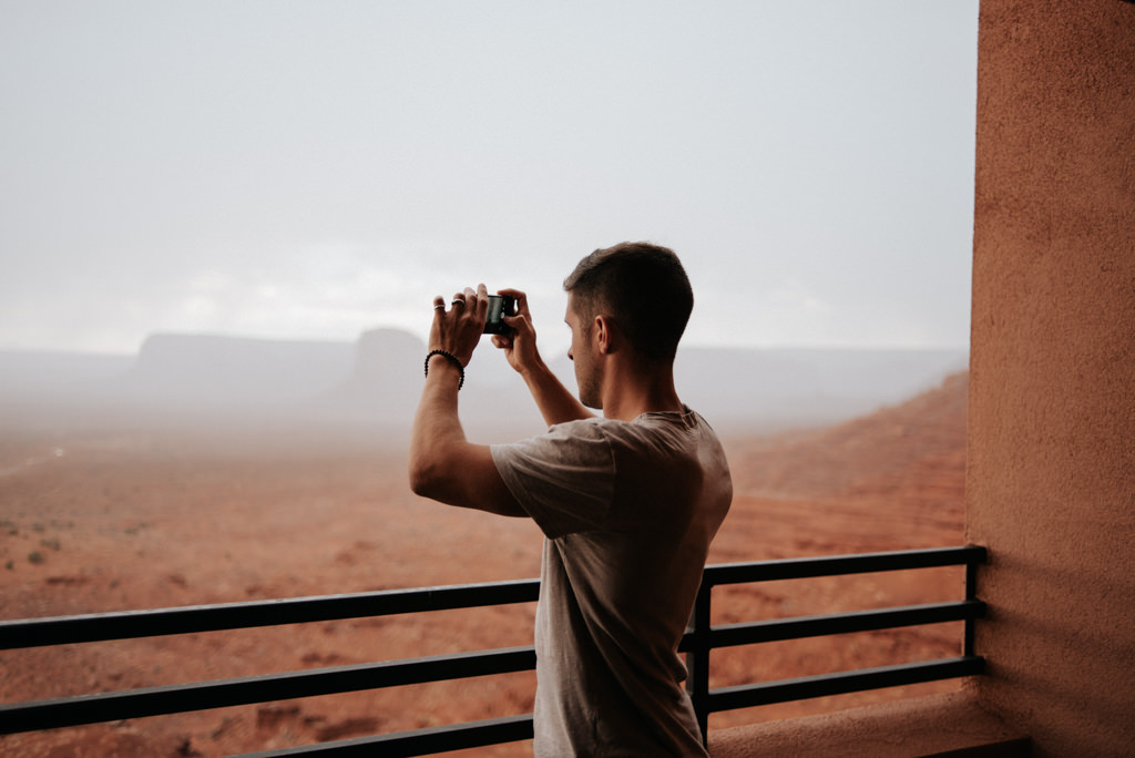 Man taking picture of Monument Valley from balcony of hotel room at the View Hotel