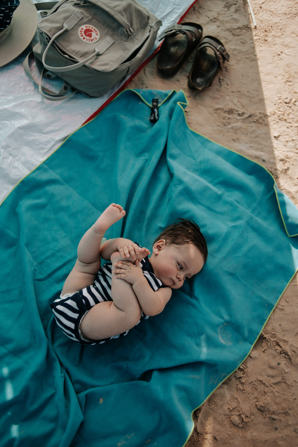 Baby boy lying on towel in shade at Glen Canyon National Recreation Area